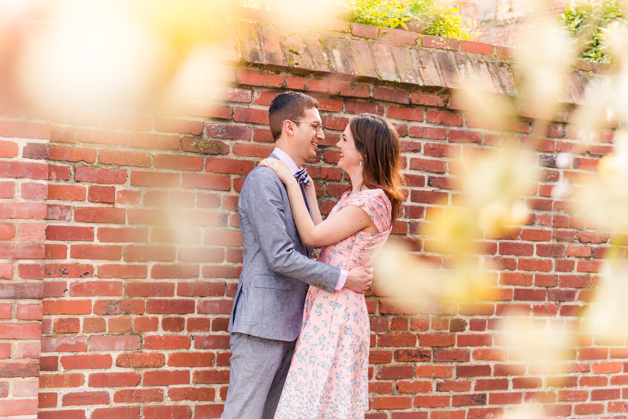 An engaged couple embraces in a secluded spot by a brick wall during their engagement session in Old Town Alexandria