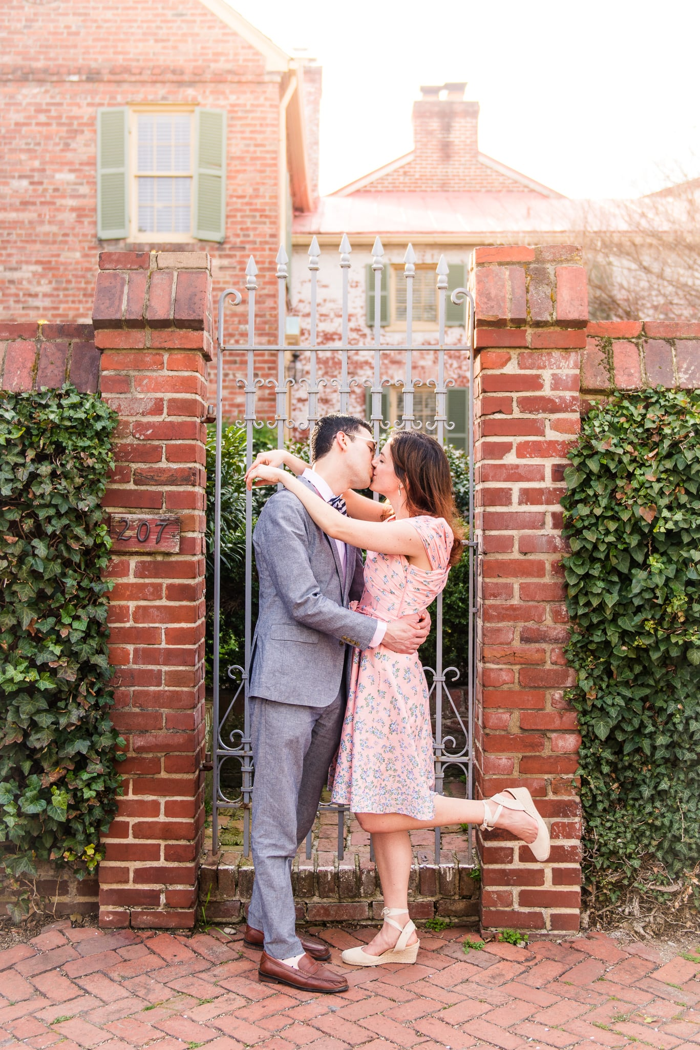 An engaged couple shares a kiss in front of a gate during their engagement session in Old Town Alexandria