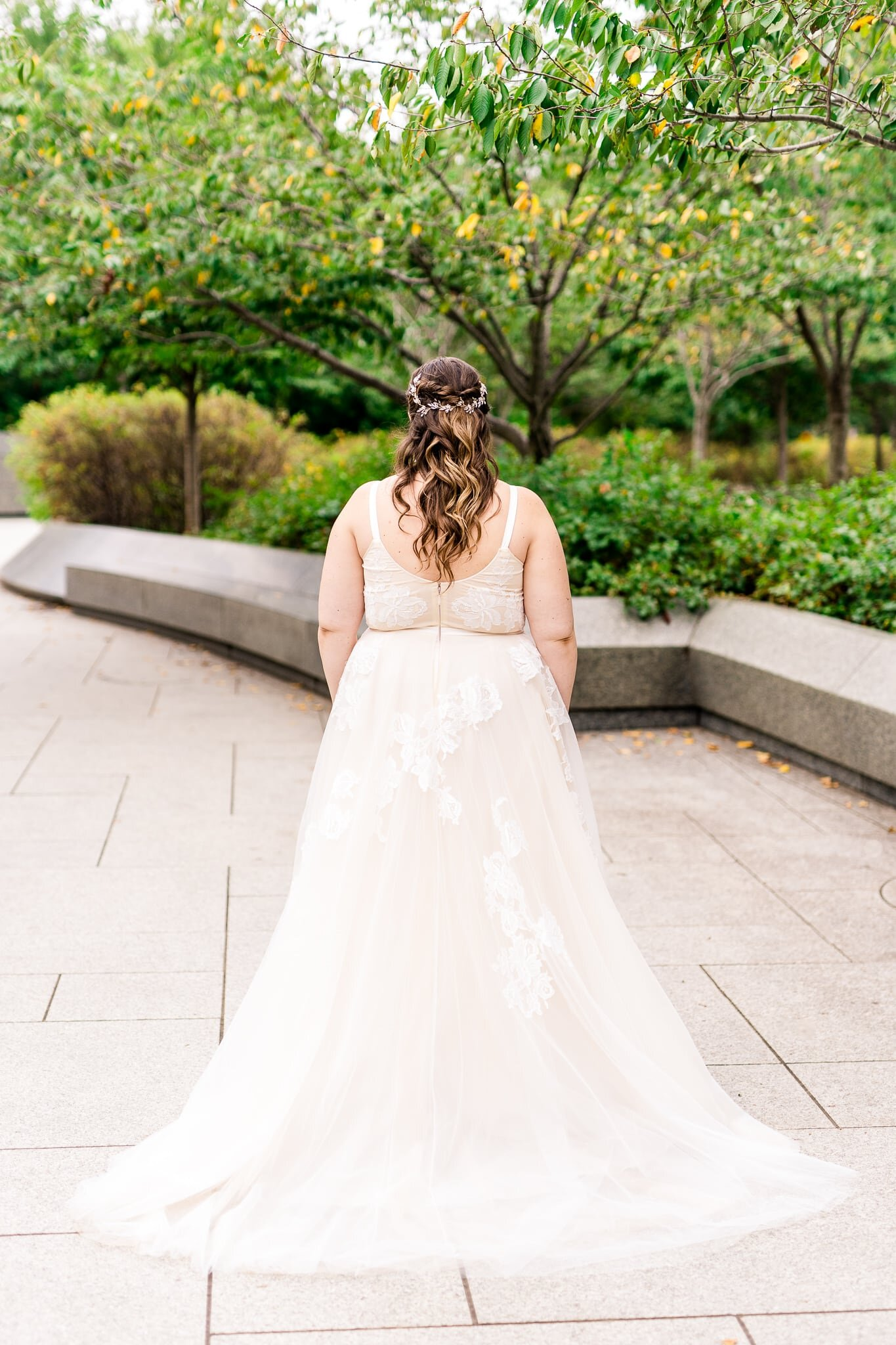 A bride faces away from the camera to show off the details on the back of her dress and her hair on her wedding day at the Tidal Basin near the MLK Memorial in Washington, DC