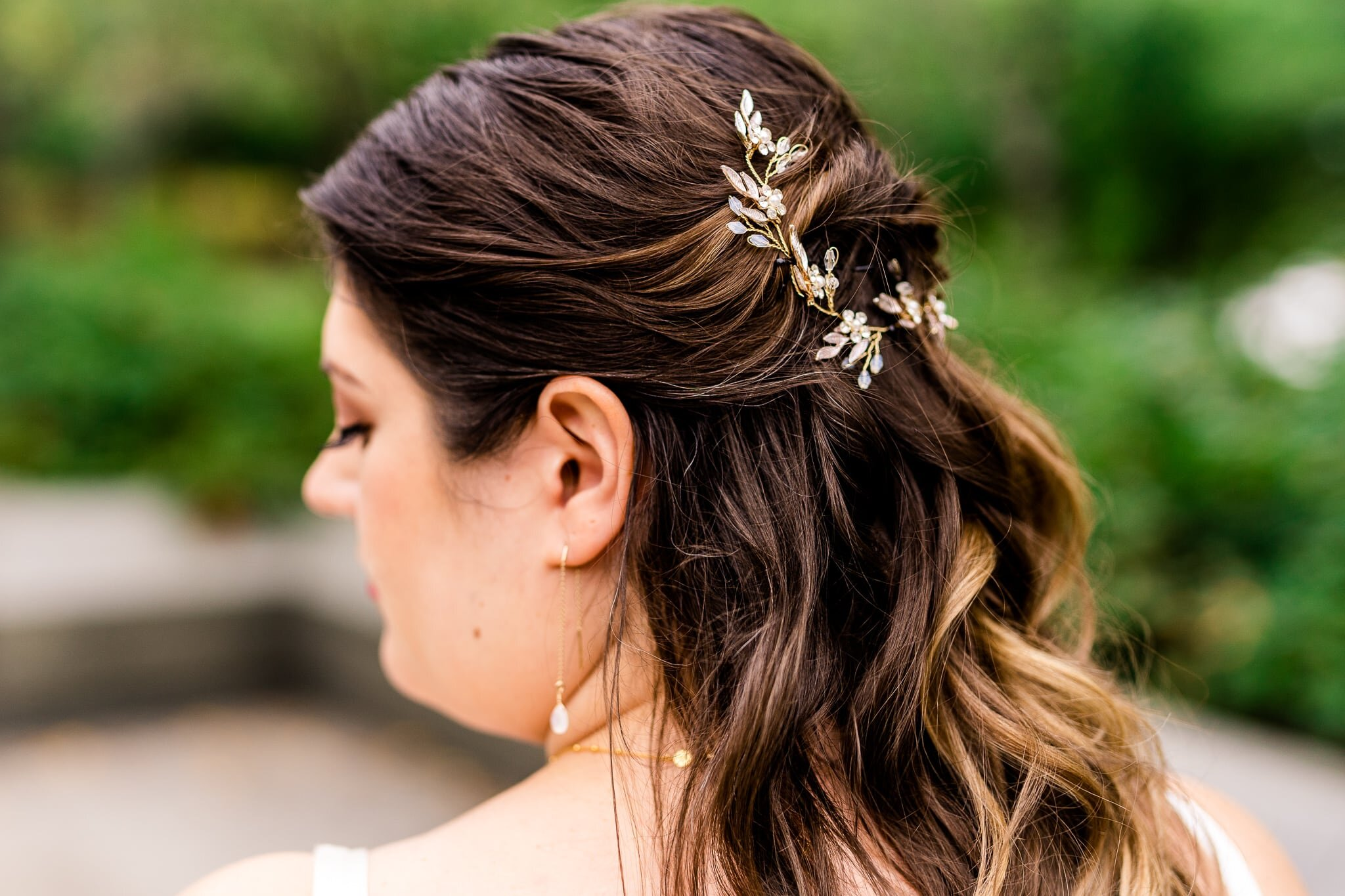 Details of a bride's jewelry including a bridal hair vine hairpiece and drop earrings on her wedding day at the Tidal Basin near the MLK Memorial in Washington, DC