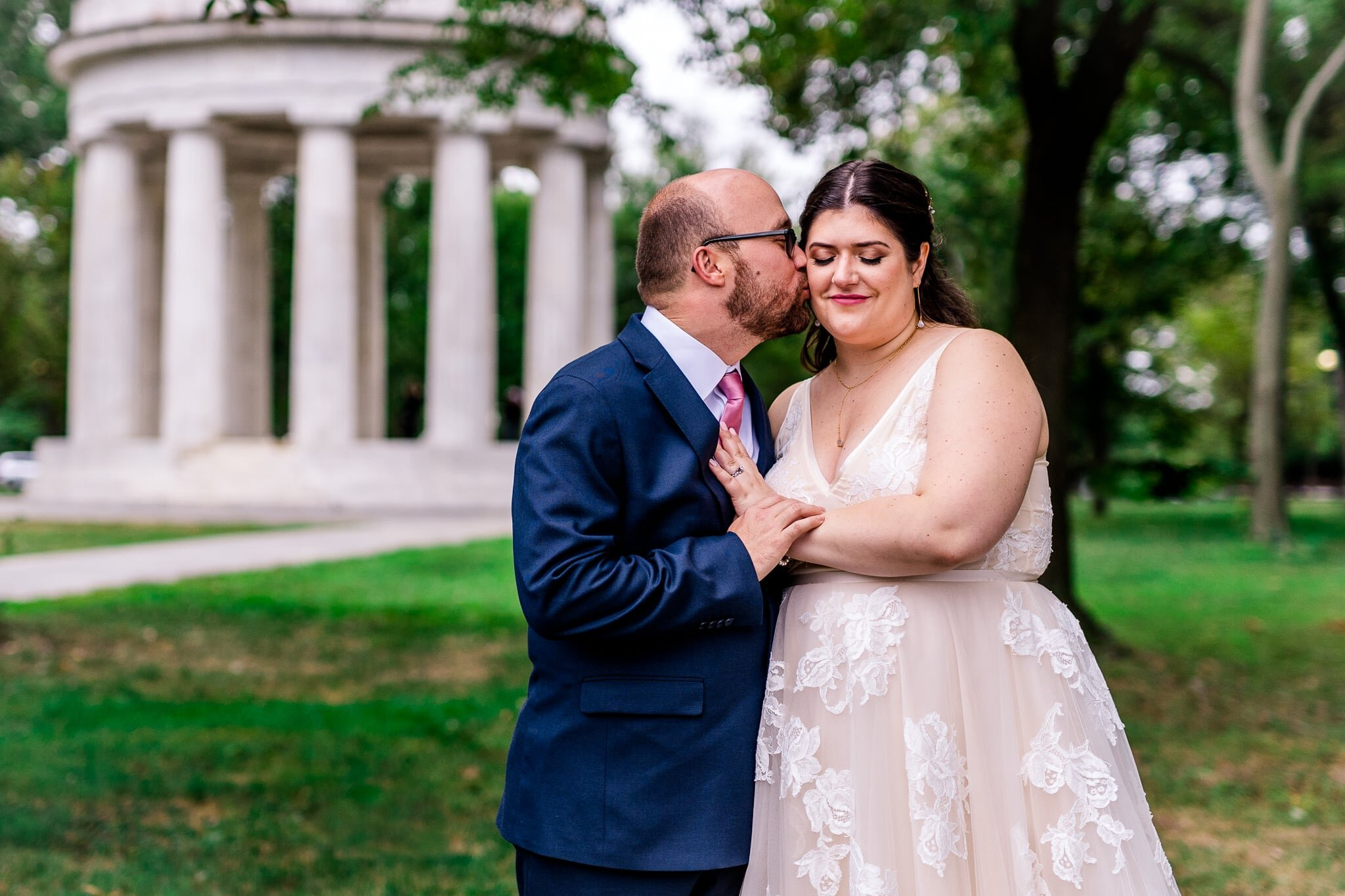 A groom kisses his bride on the cheek on their fall wedding day in front of the DC War Memorial in Washington, DC