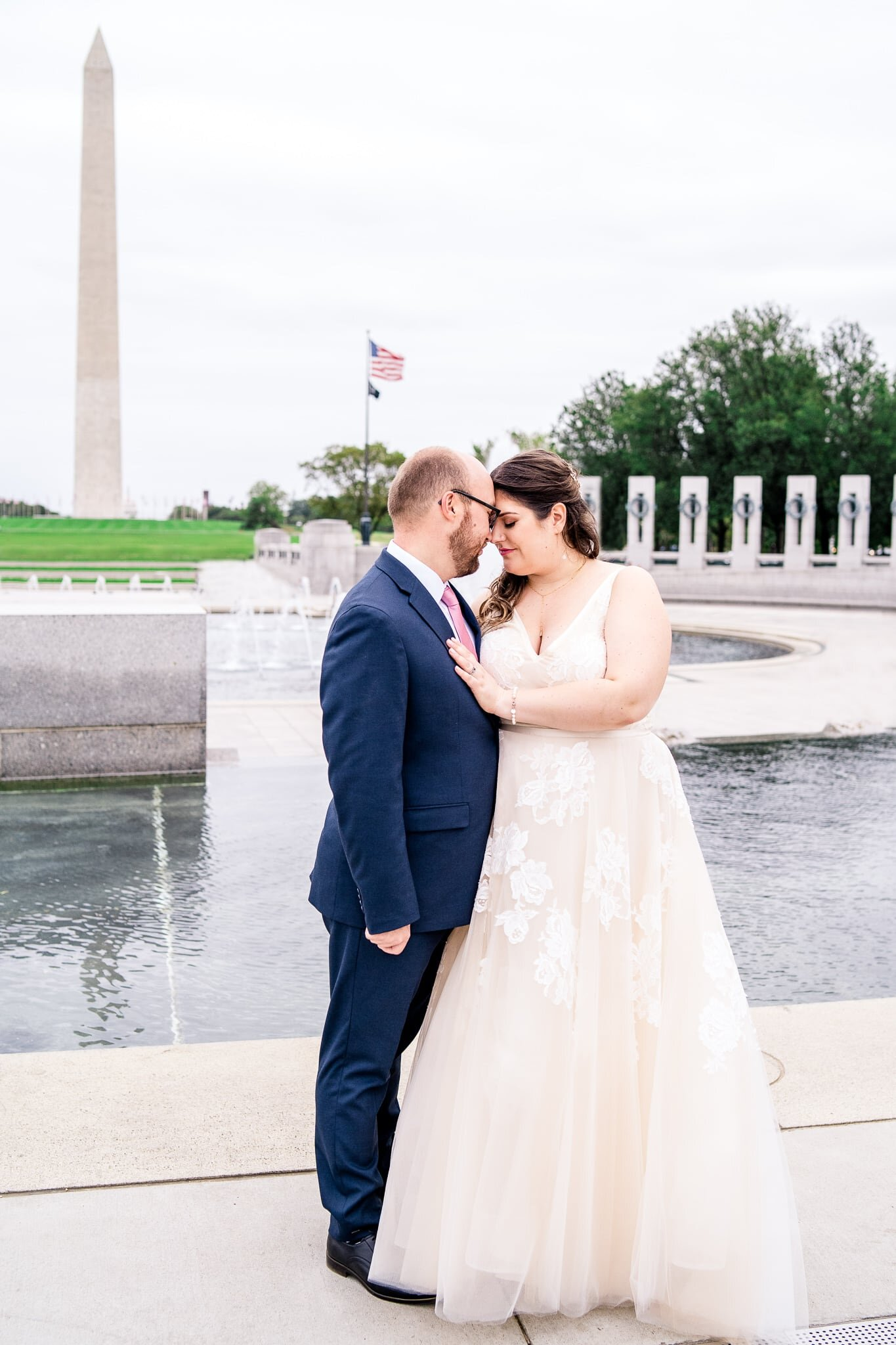 A bride and groom stand together with foreheads together on their fall wedding day at the WWII Memorial in front of the Washington Monument in Washington, DC