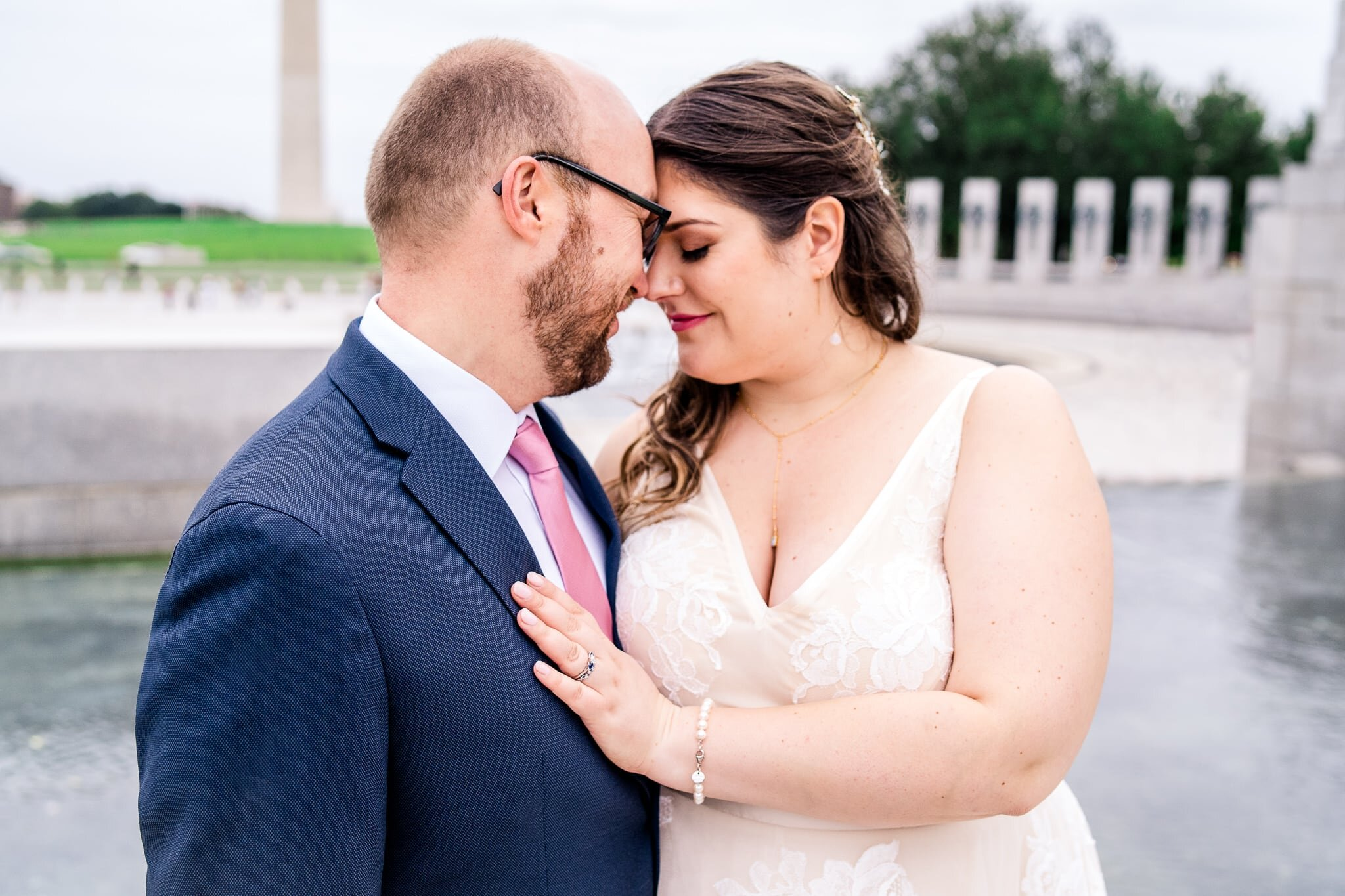 A bride and groom stand together with foreheads together and her hand on his chest on their fall wedding day at the WWII Memorial in front of the Washington Monument in Washington, DC
