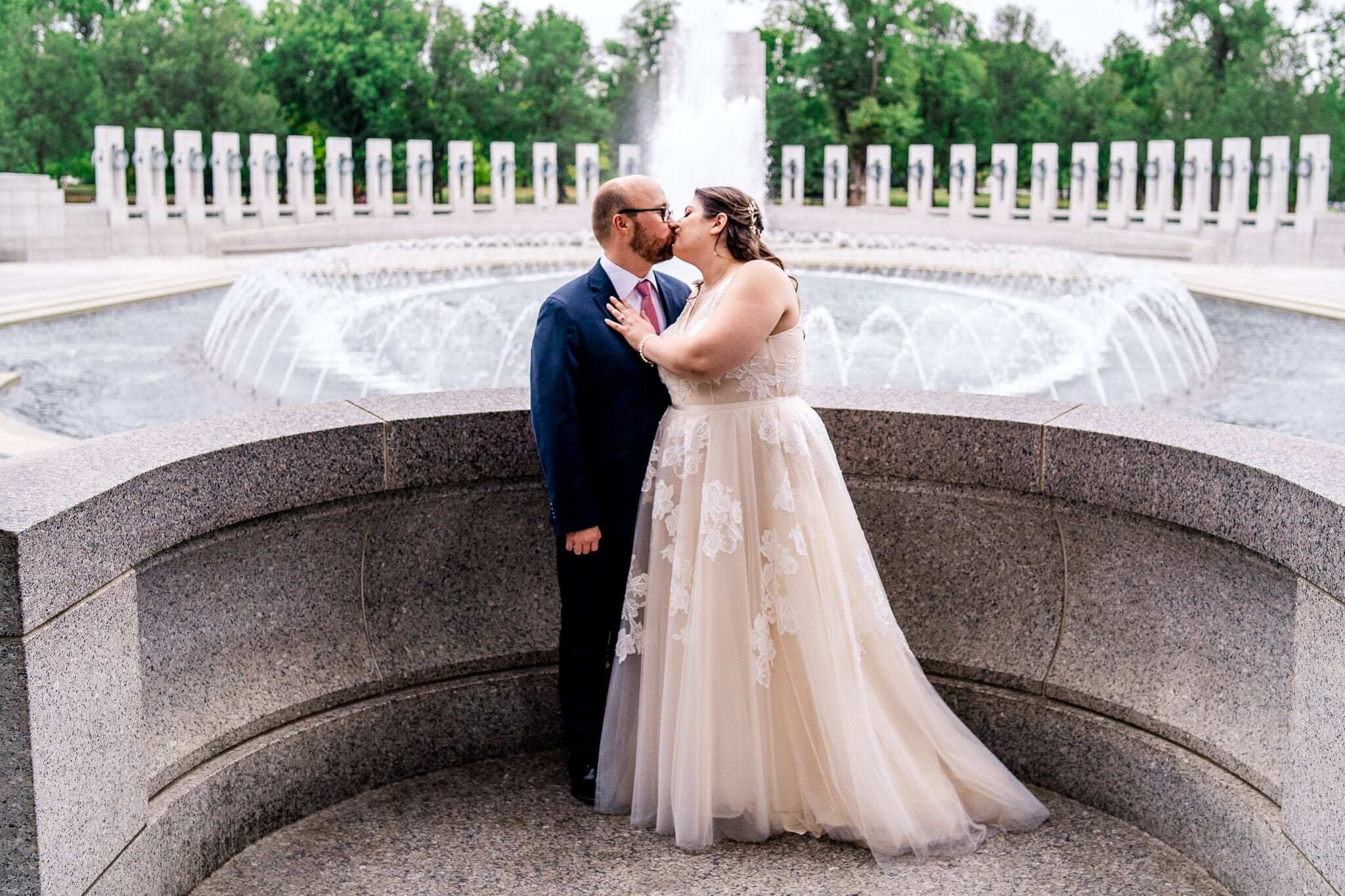 A bride and groom share a kiss on their fall wedding day at the WWII Memorial in Washington, DC