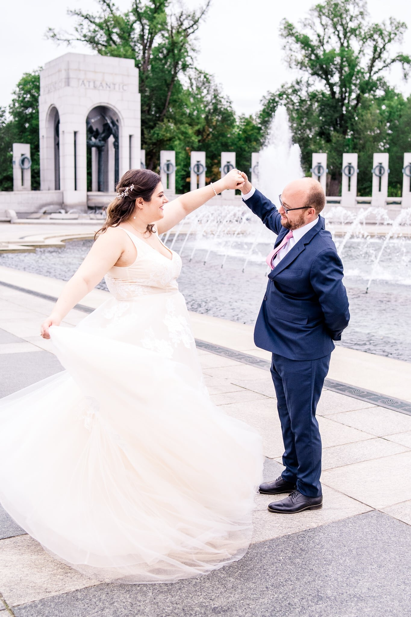 A groom twirls his bride as her tulle wedding dress swirls around her on their fall wedding day at the WWII Memorial in Washington, DC