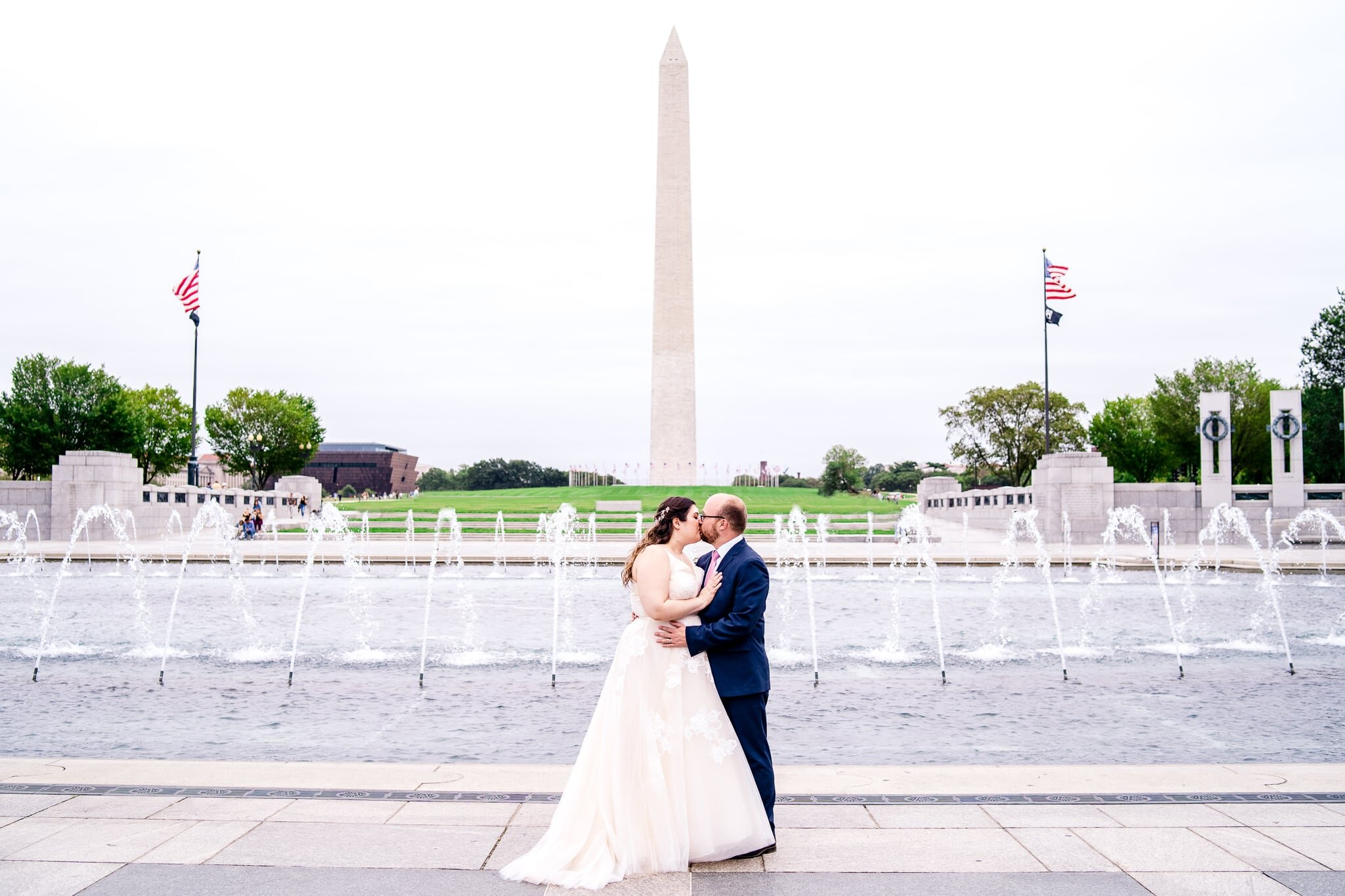 A bride and groom share a romantic kiss on their fall wedding day at the WWII Memorial in front of the Washington Monument in Washington, DC