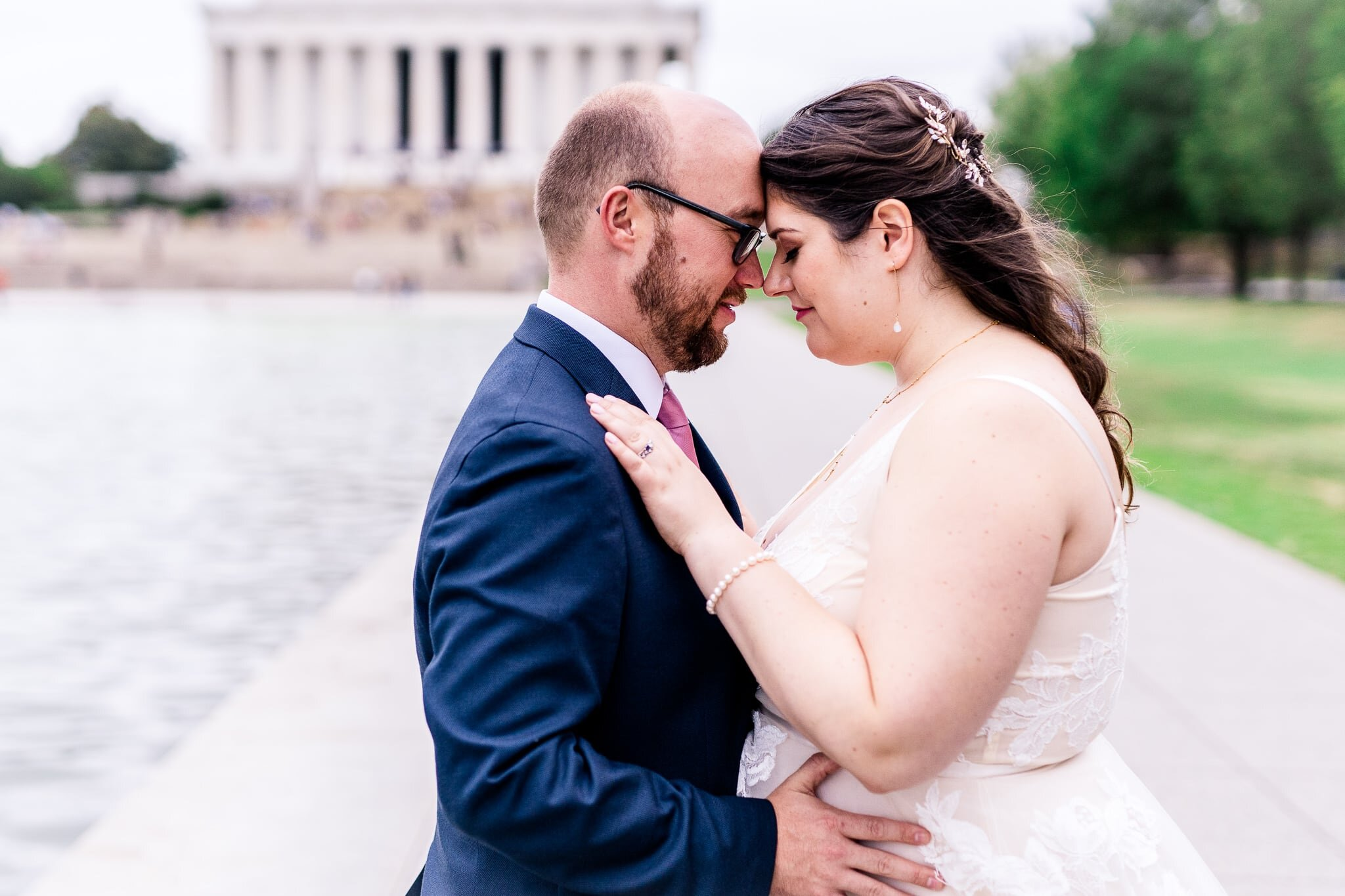 A bride and groom pose together with foreheads and noses together on their fall wedding day at the Reflecting Pool in front of the Lincoln Memorial in Washington, DC