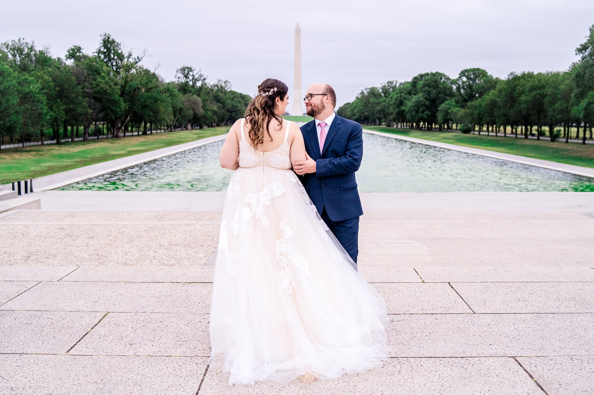 A bride faces away as her groom faces toward the camera and they look at each other as her tulle dress blows gently in the breeze on their fall wedding day at the Reflecting Pool in front of the Lincoln Memorial and Washington Monument in Washington, DC
