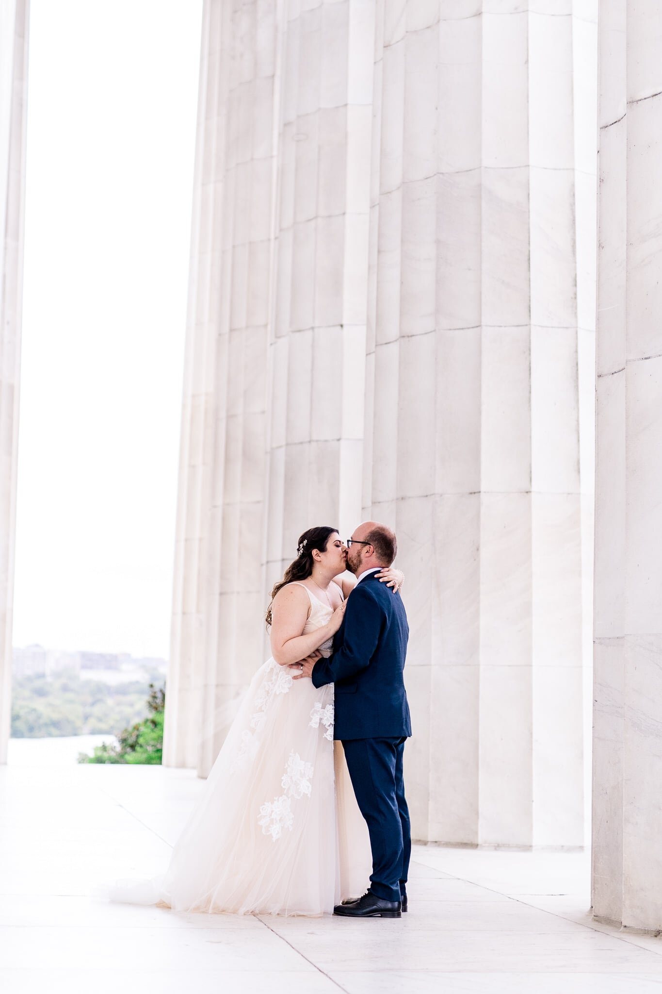 A bride and groom dance together and share a kiss on their wedding day at the Lincoln Memorial in Washington, DC