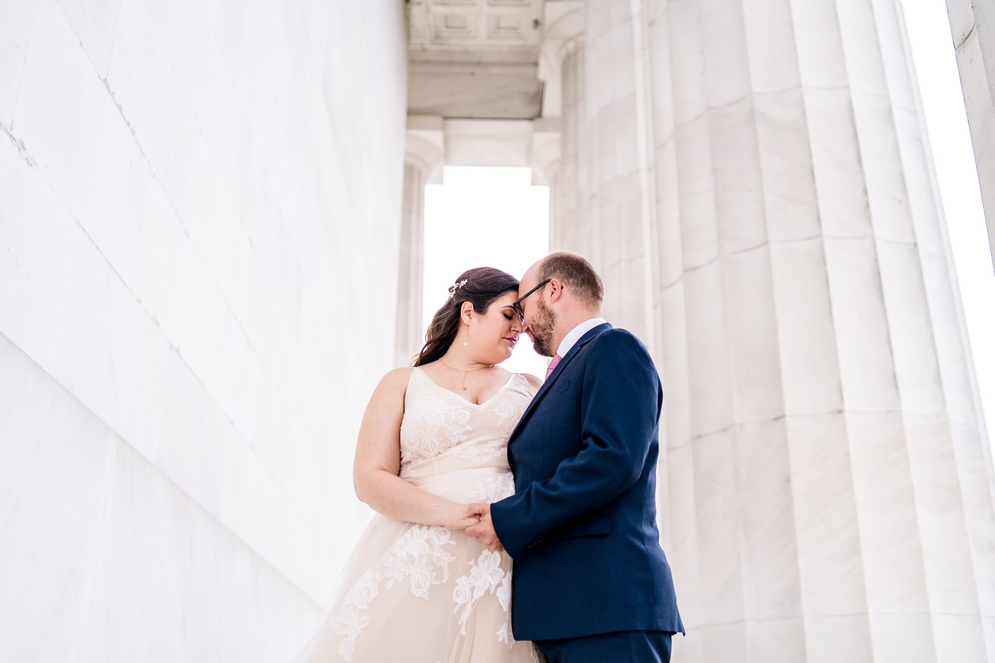 A bride and groom stand together with foreheads together holding hands on their wedding day at the Lincoln Memorial in Washington, DC
