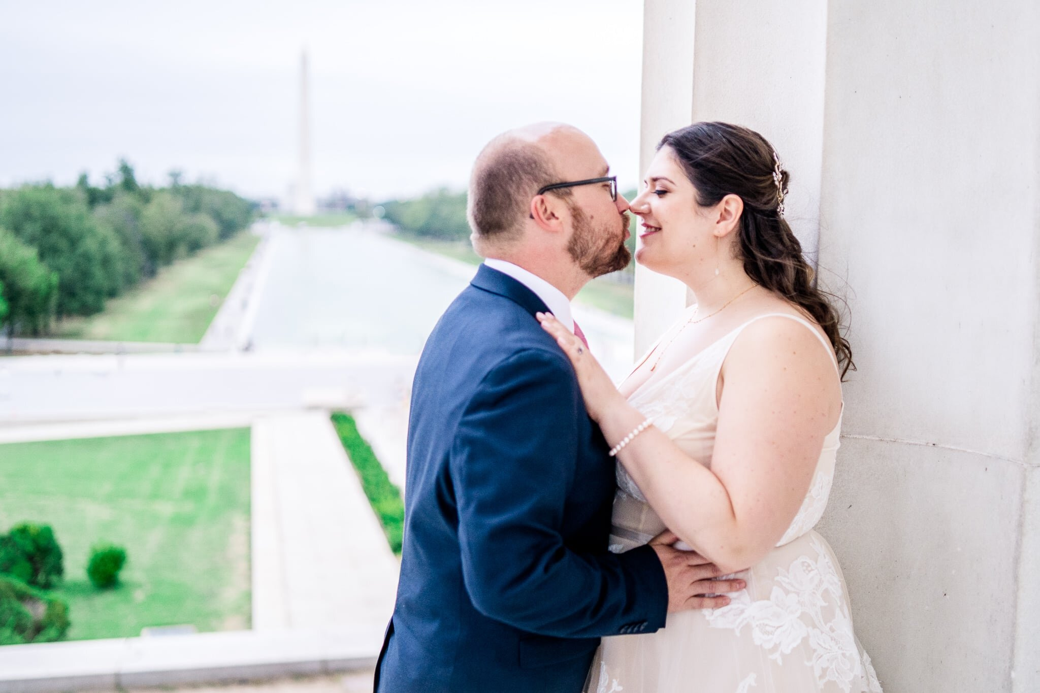 A bride and groom snuggle in together beside a marble column on their wedding day with a view of the reflecting pool and Washington Monument at the Lincoln Memorial in Washington, DC
