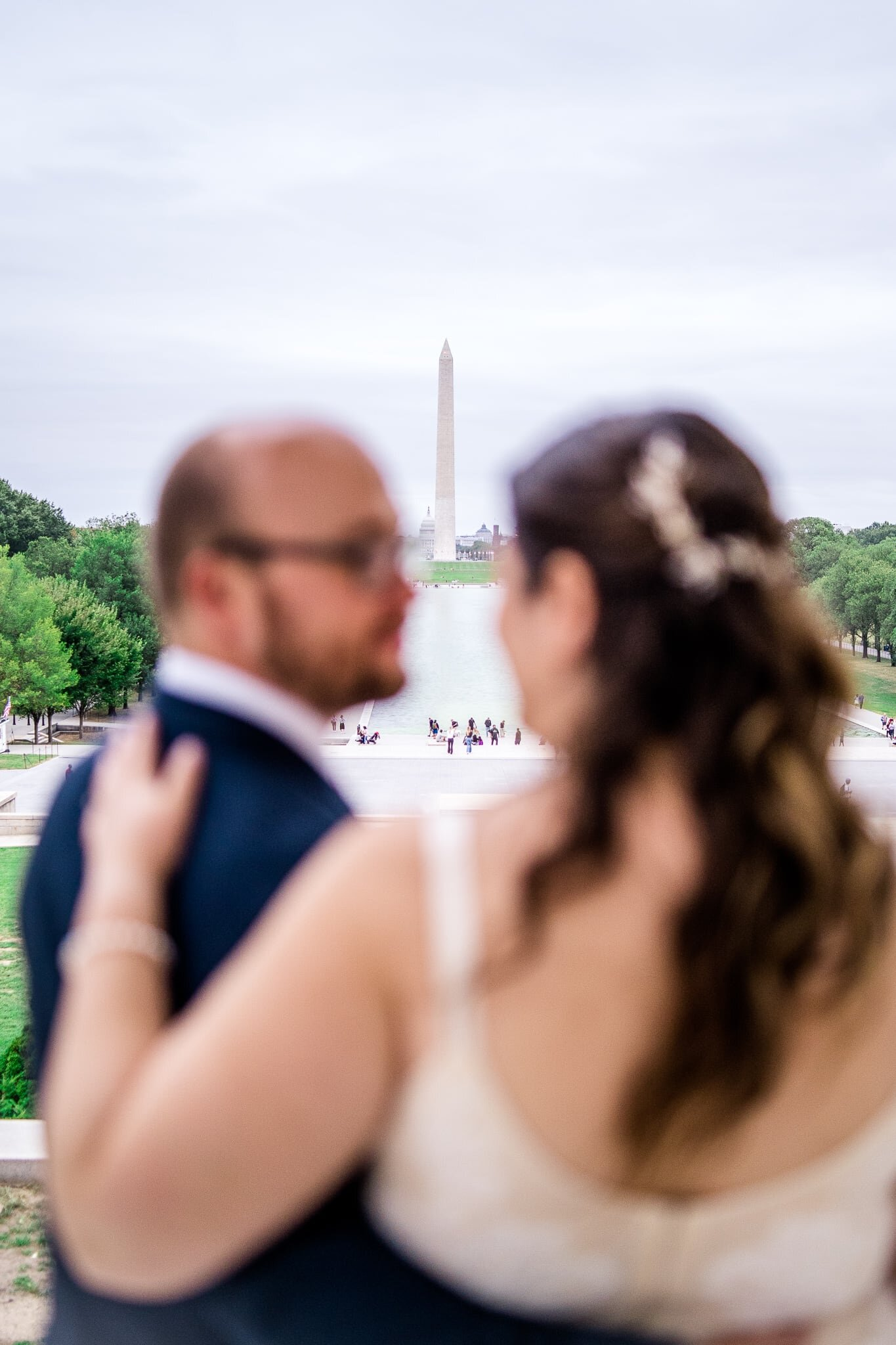 A bride and groom embrace and look at each other in front of a view of the reflecting pool and Washington Monument at the Lincoln Memorial in Washington, DC