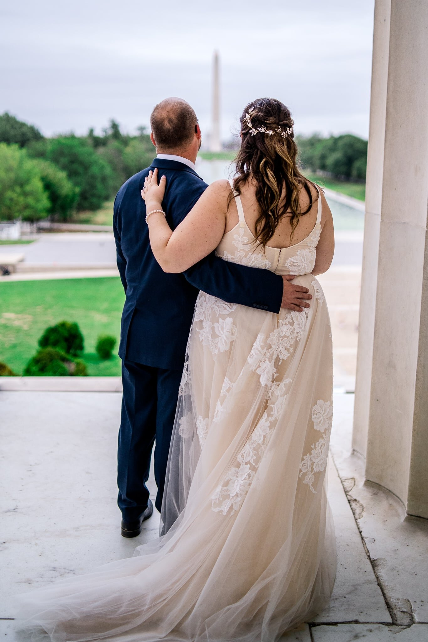 A bride and groom embrace and enjoy a view of the reflecting pool and Washington Monument at the Lincoln Memorial in Washington, DC