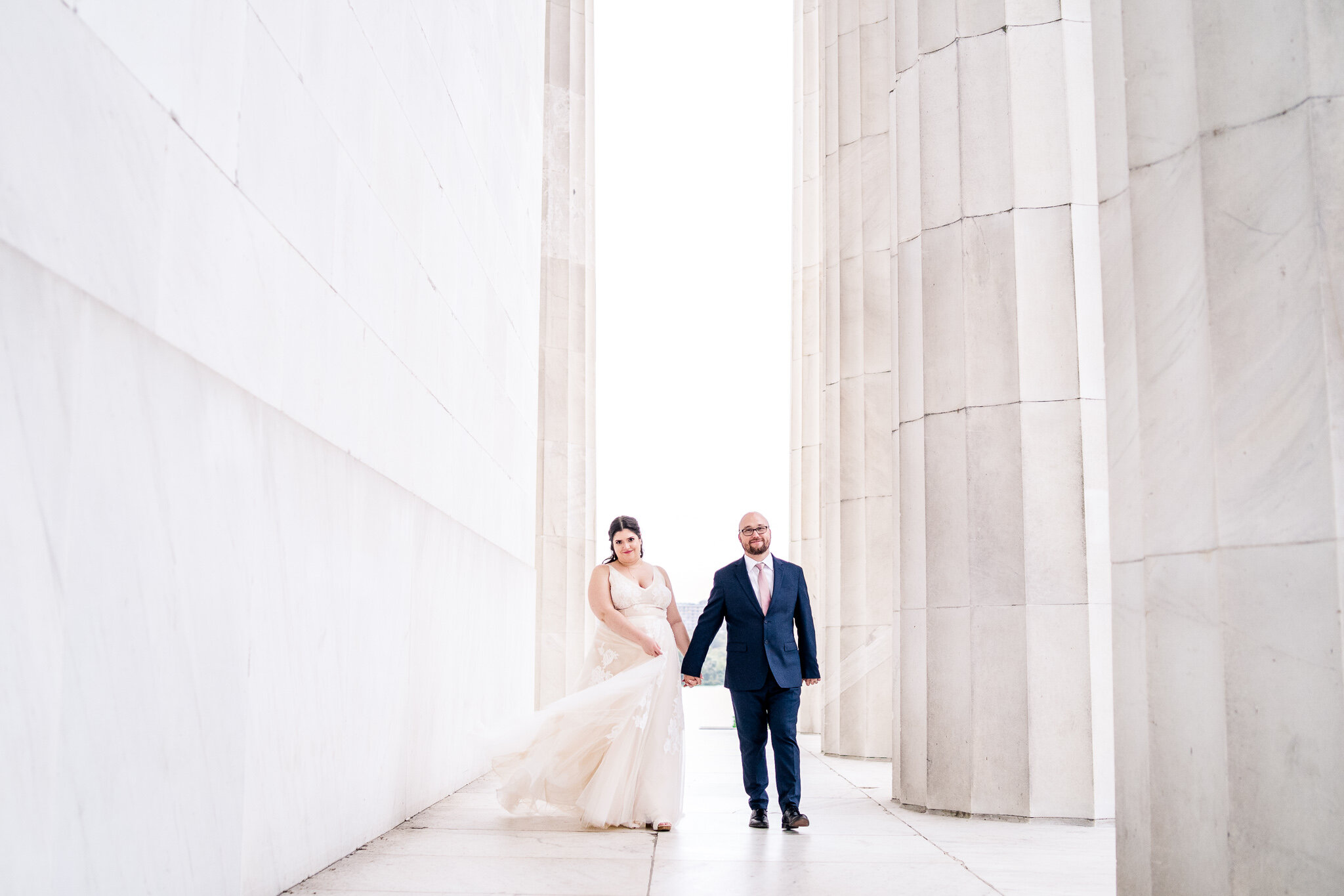 A bride and groom walk together along the columns of the Lincoln Memorial as her tulle skirt flows around her on their wedding day in Washington, DC