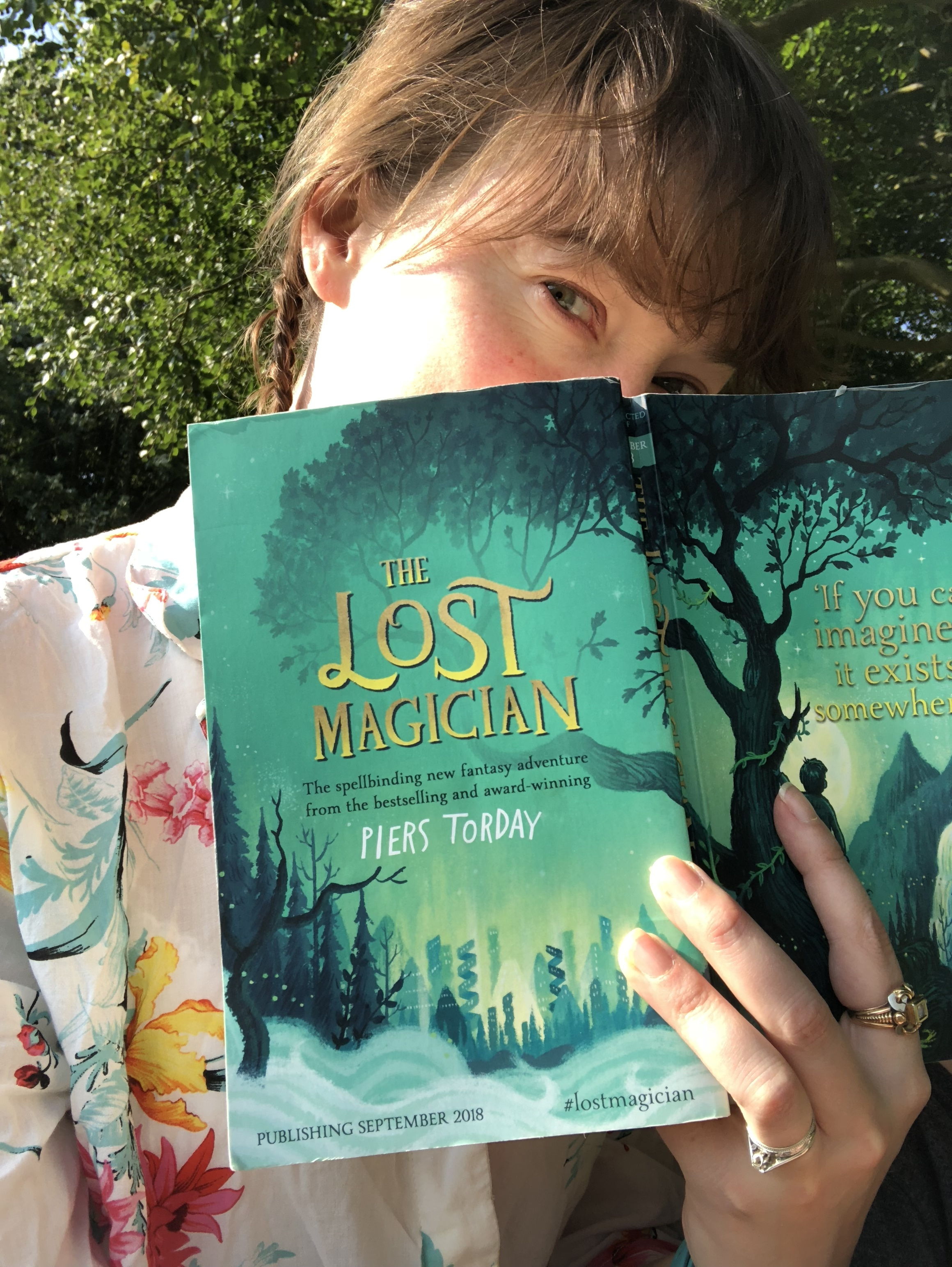 Me reading  The Lost Magician  in a field on the edge of a woods. Magic.