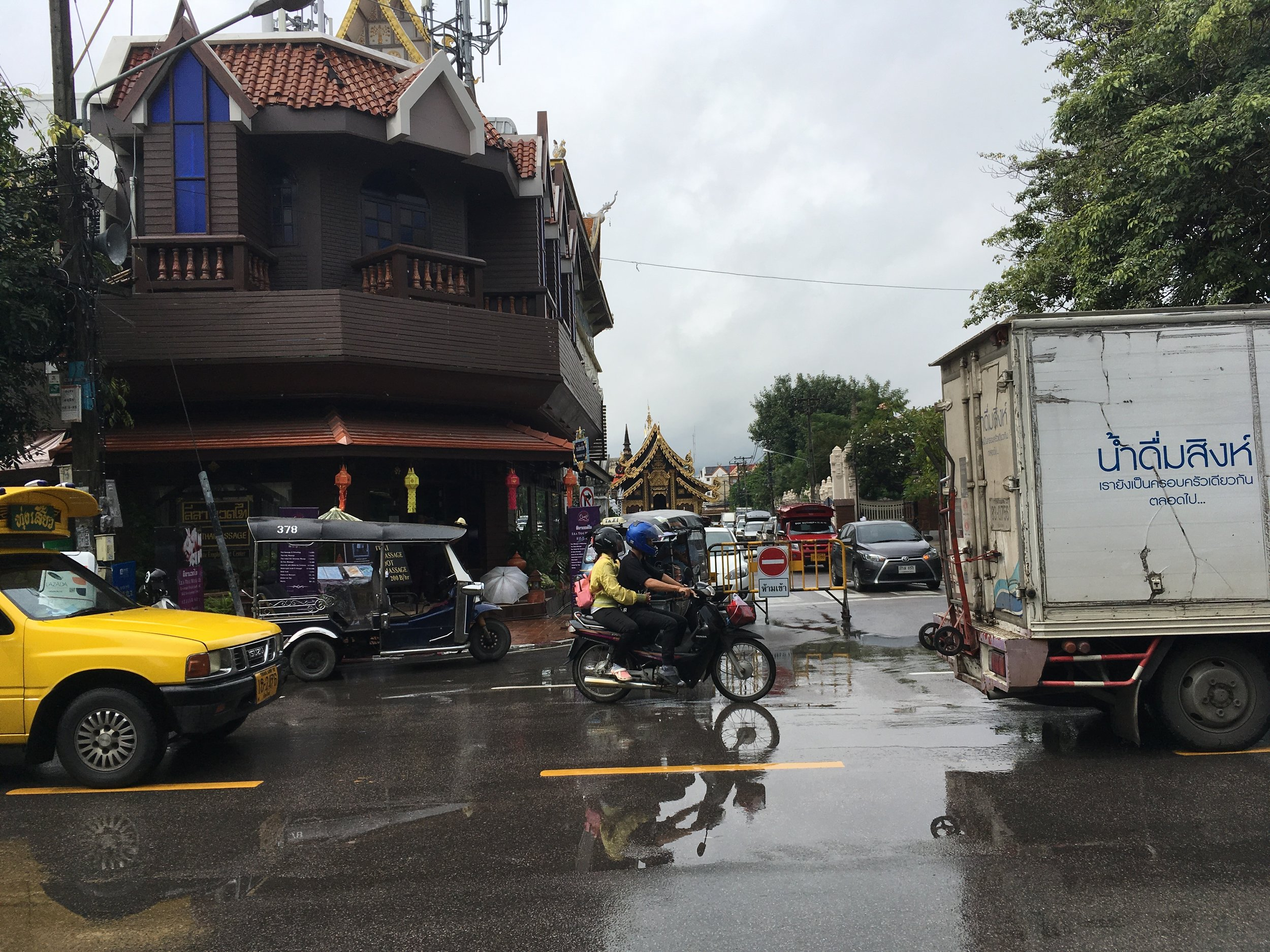 Tuk tuk is the blue one in front of the building
