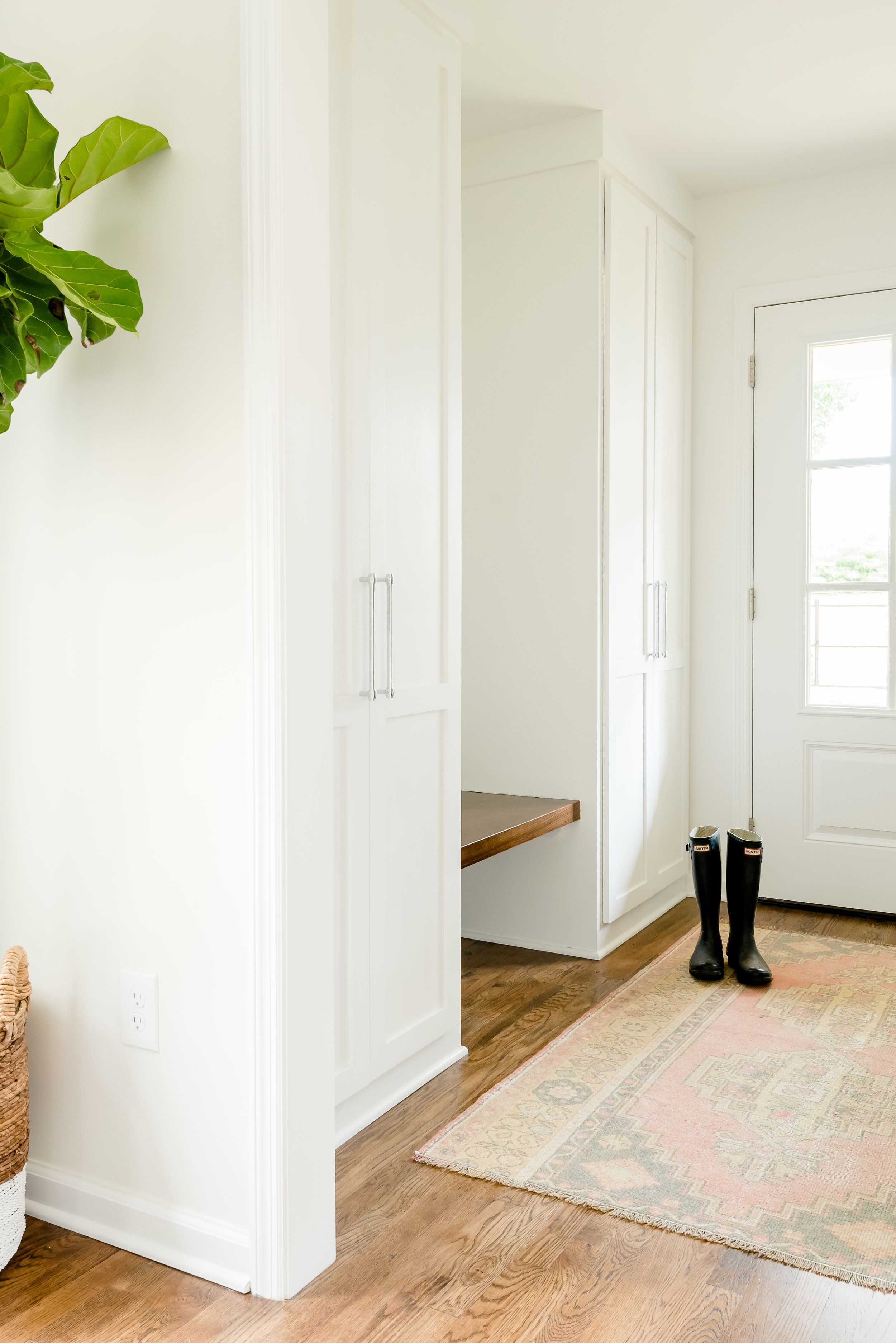 custom mudroom with twin wardrobes and a floating bench made of ash.