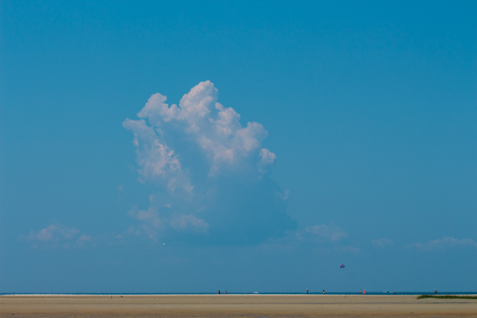 A lone cloud in the crystal blue sky