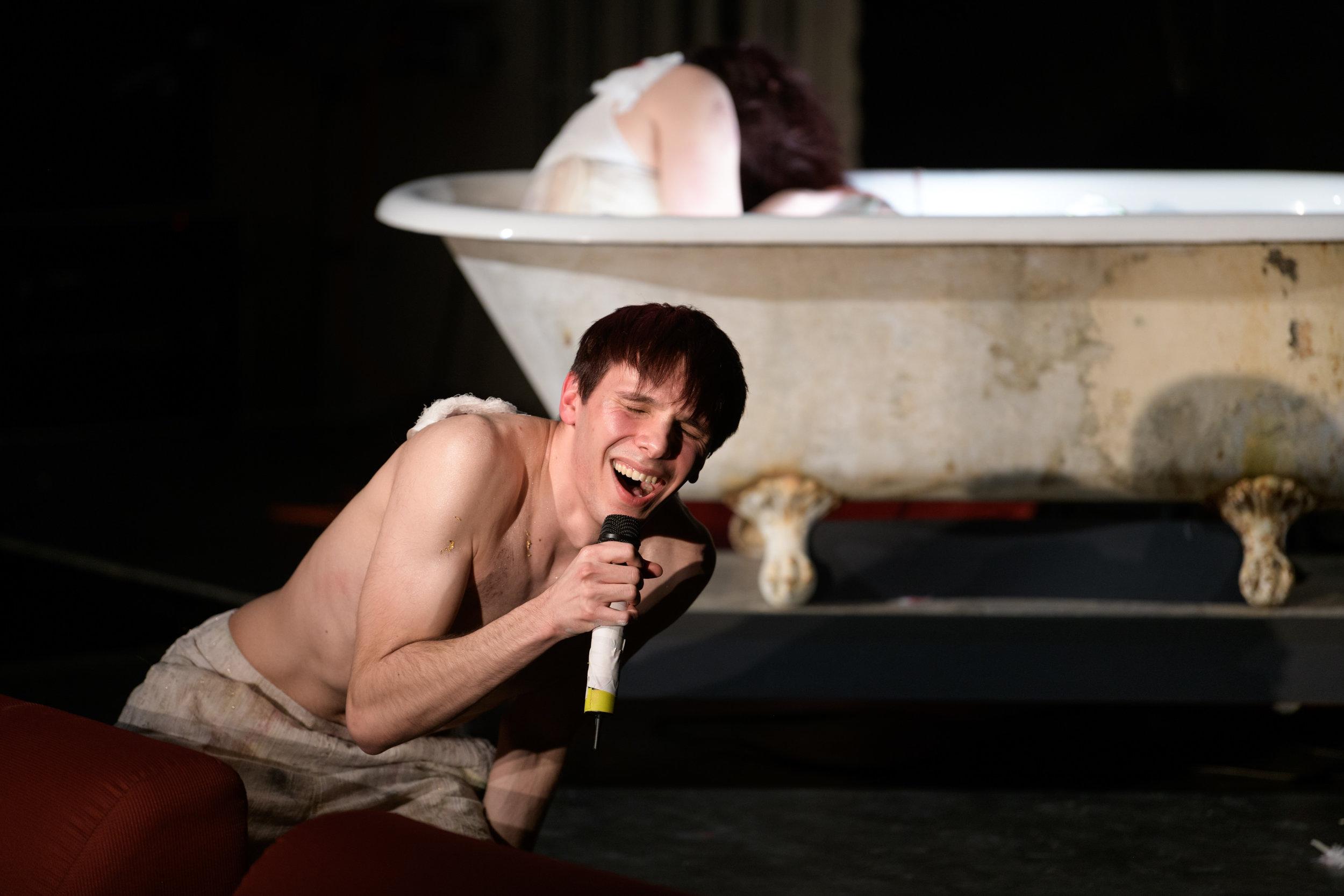 Nicholas Music, as Boy Angel, sings on stage in  Angel's Bone