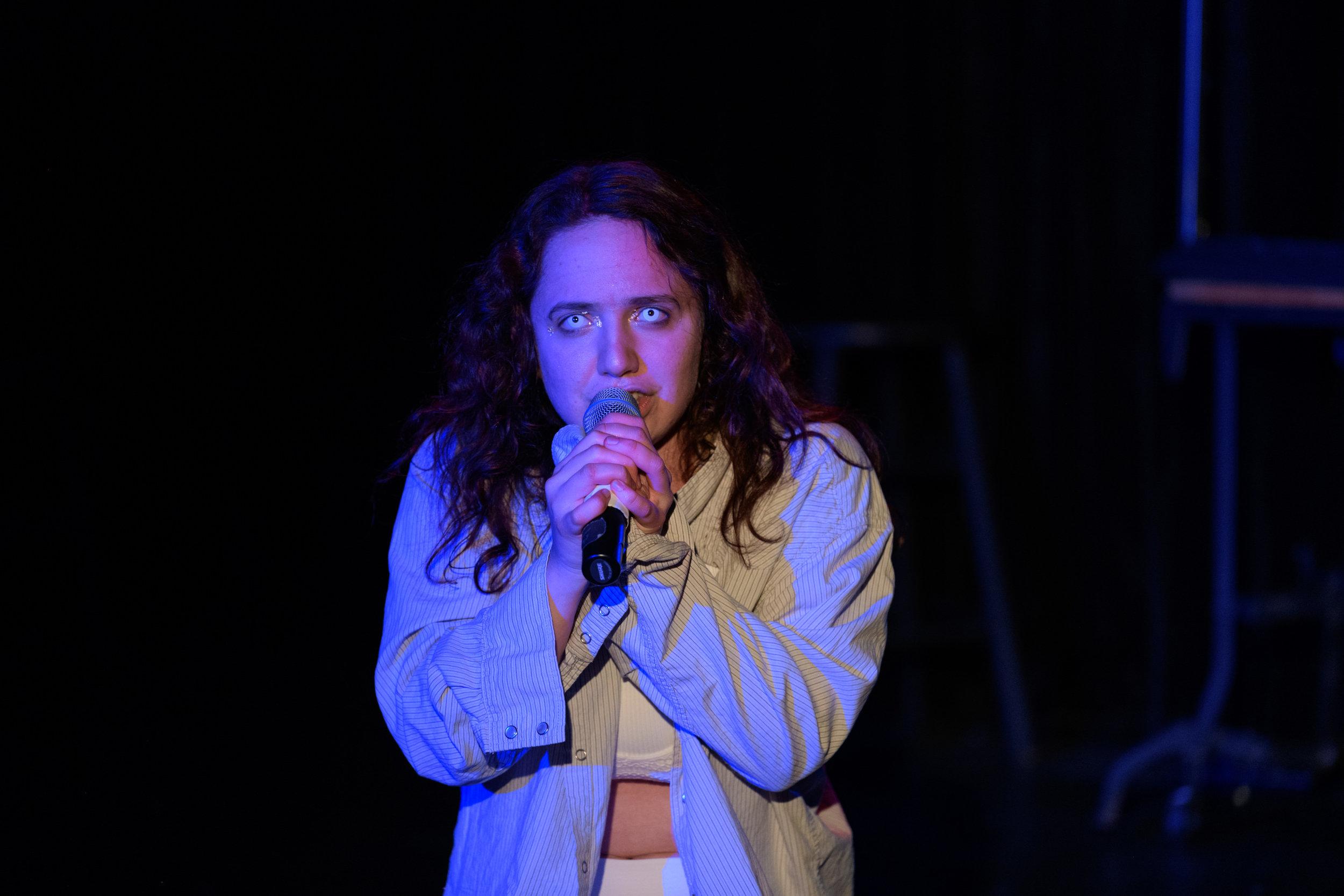 Chloe Falkenheim, as Girl Angel, sings a solo. Note her eyes.