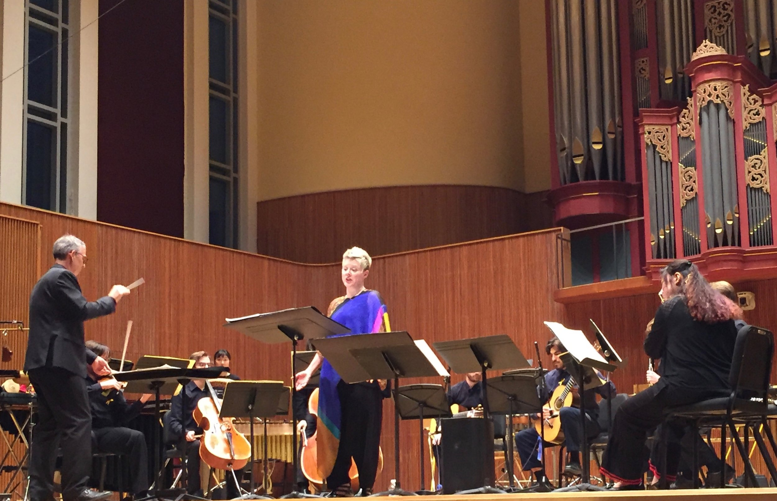 Tim Weiss conducts, Tony Arnold sings; guitarist Mohit Dubey partially visible.