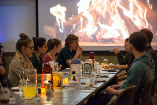 Students sitting at a dining table with a video of a fire projected behind them.
