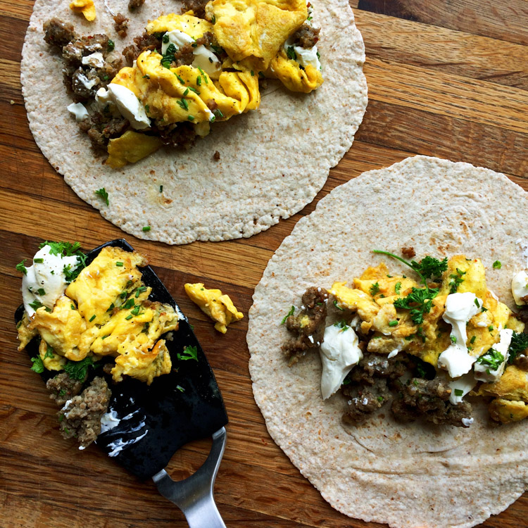 Roll a low carb breakfast burrito with sausage, eggs, and cheese. Low carb keto wrap for breakfast.