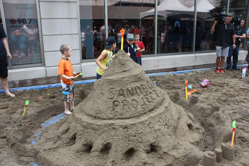 Some of the kids stand next to a sandcastle bigger than them