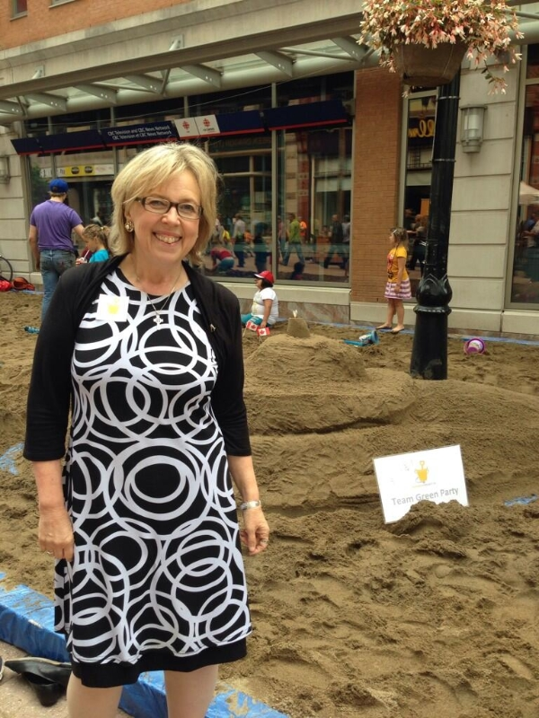 MP Elizabeth May infront of the Team Green Party Sandcastle