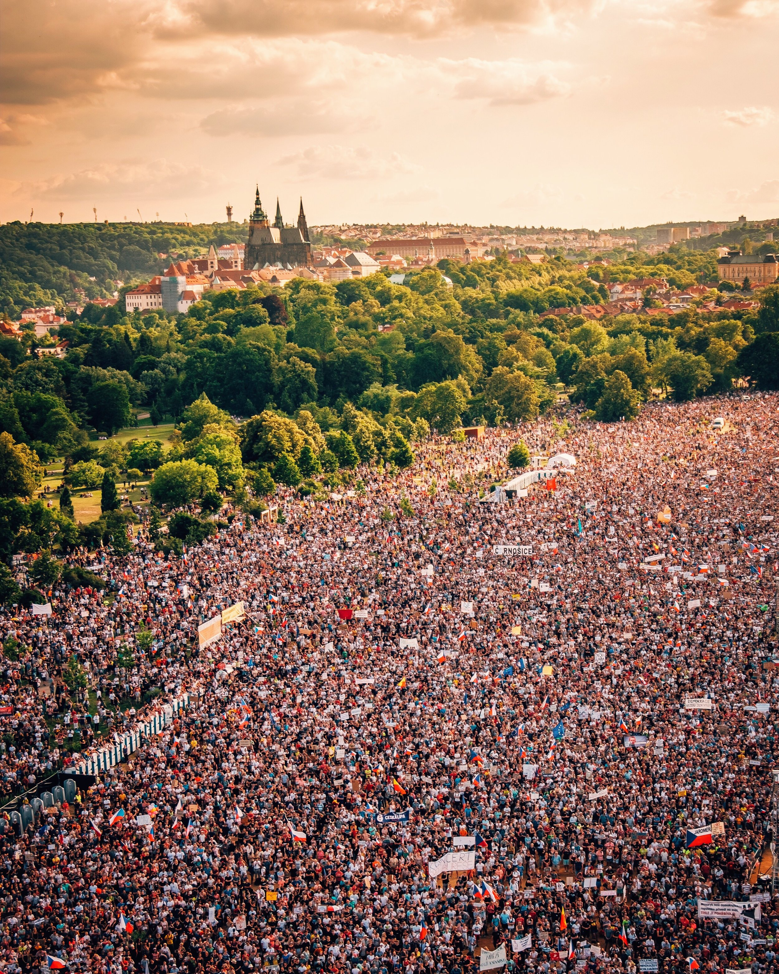 View from above of crowds protesting at Letna Park with Prague Castle as backdrop