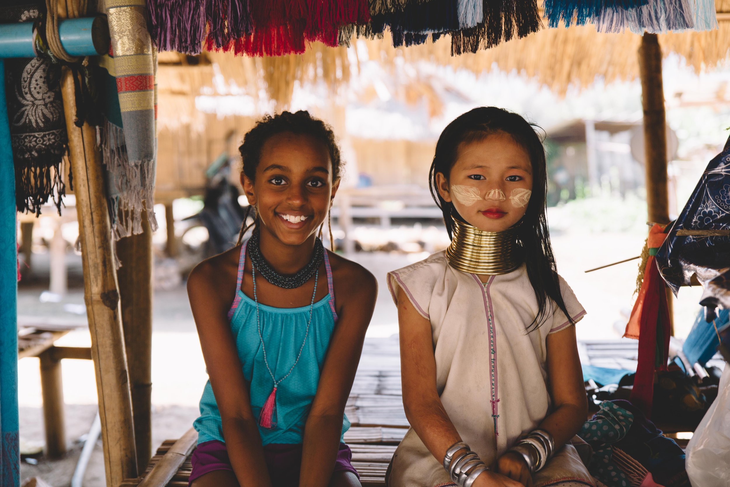 While in Chiang Rai, Thailand we had the opportunity to visit the Karen Long Neck tribe village and meet this beautiful 9 year old girl. Kya was immediately drawn to her, being the same age. We learned many children from the village will never attend school, instead they learn at a very young age how to hand knit scarves and other items to help their family earn an income. The villagers have placed rings around the girl's necks, to protect from tigers who may enter the village seeking prey. Village stories tell of a young girl who was bitten by a tiger on her neck and killed many years ago.