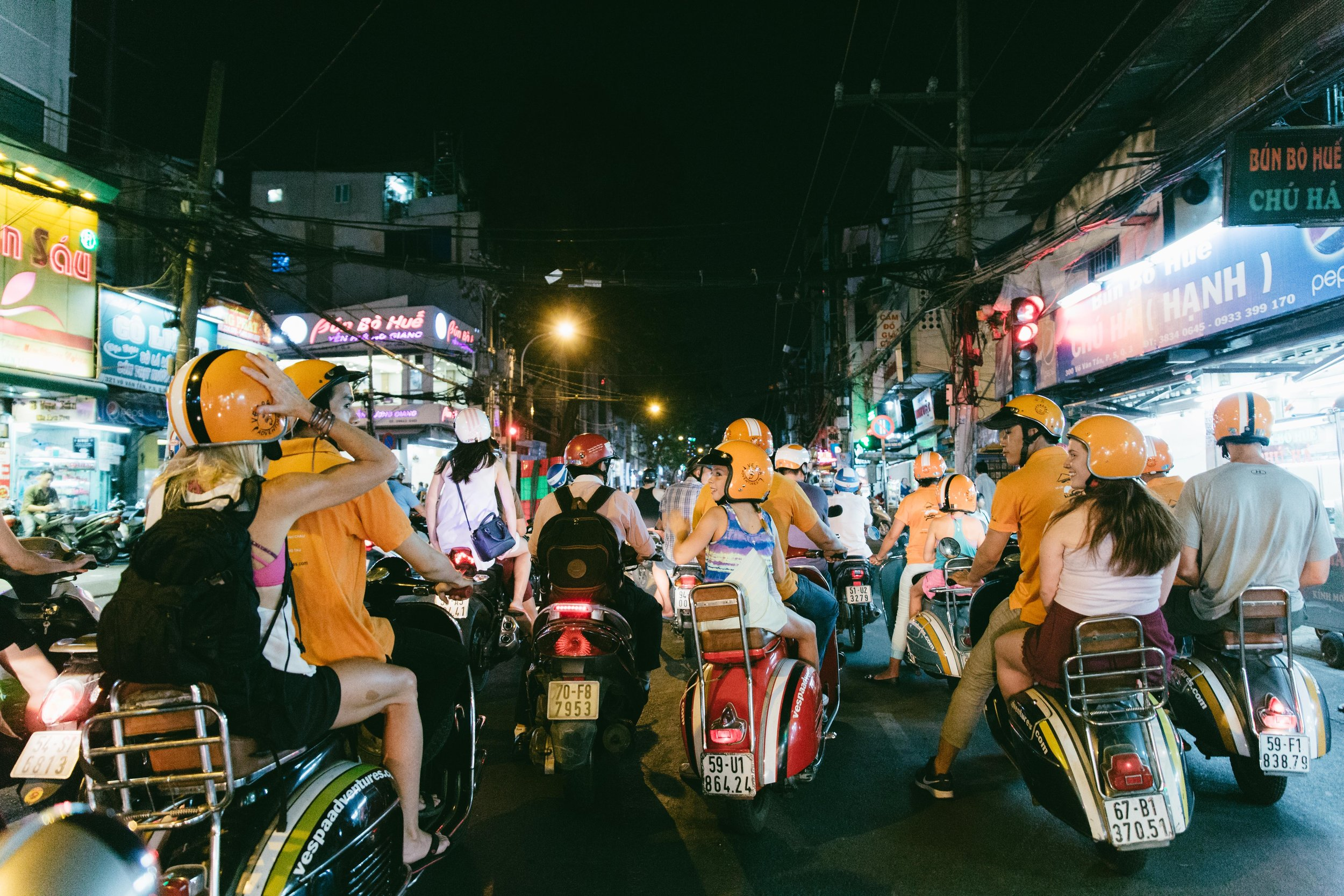 What better way to take in the sights, sounds, and feel of a new city then to hop the back of 6 scooters for a  tour of Saigon after dark. In a city with over 10 million people and 8 million scooters, it is pretty much the only option to get around. We spent the evening trying local street food, seeing famous landmarks, and laughing constantly as we zigged and zagged all over the city.  At this red light, we share a laugh, tighten our helmets and do a quick head count to make sure we have everyone!