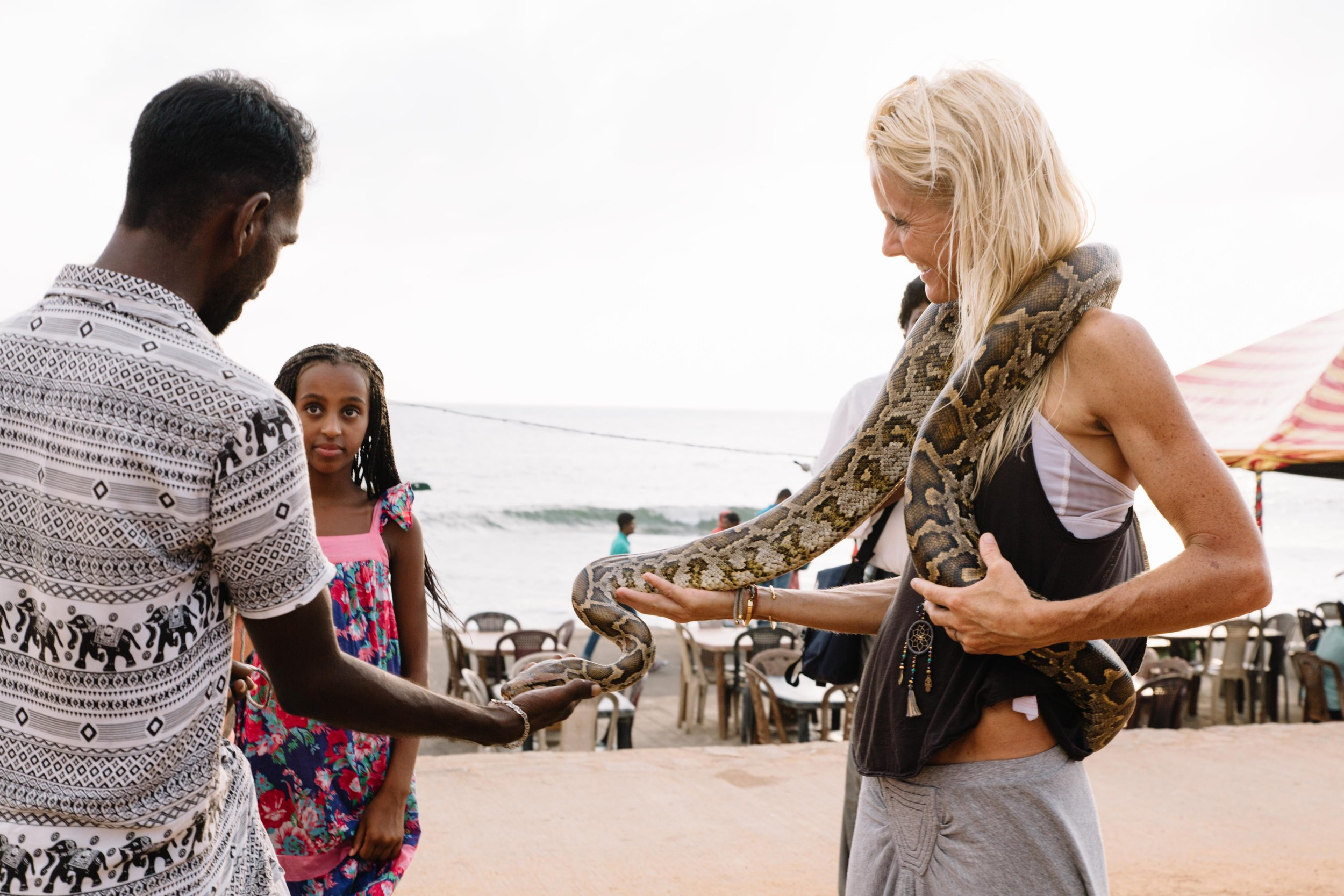 "On our first night in Colombo, Sri Lanka we ran into this ""snake-charmer"" on our way to dinner. After being talked into it for a little while, we held 7 foot pythons and Mom even faced her fear and put one around her neck. I don't think Kya will ever forget this memory!"
