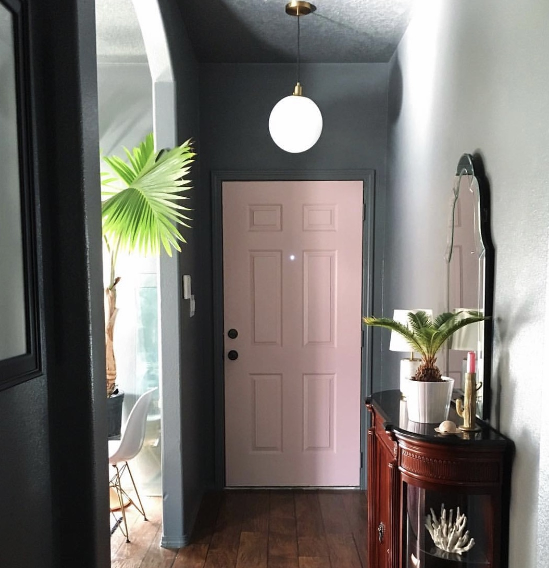 Nichol Naranjo  has effectively combined dark walls with a pop of pale pink for her front door.
