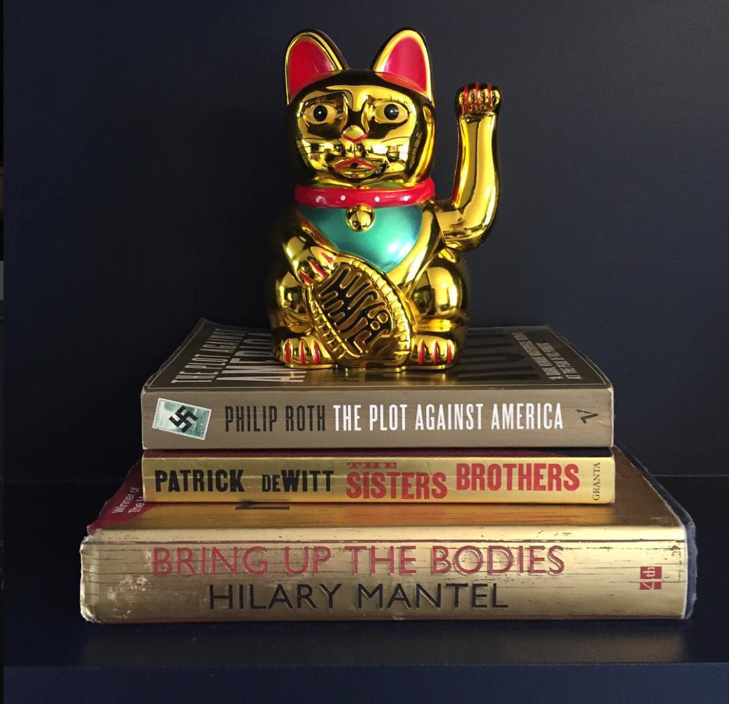Simple but effective - using books to create height and adding a bit of much needed quirkiness with the Chinese cat, tied together in gold. Jess Hurrell of  Gold Is A Neutral .