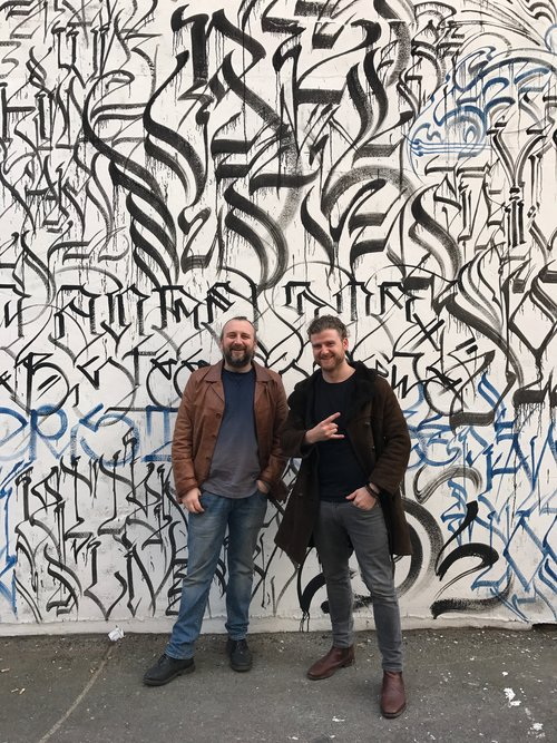 Craig and Jeff in front of artwork by Defer.