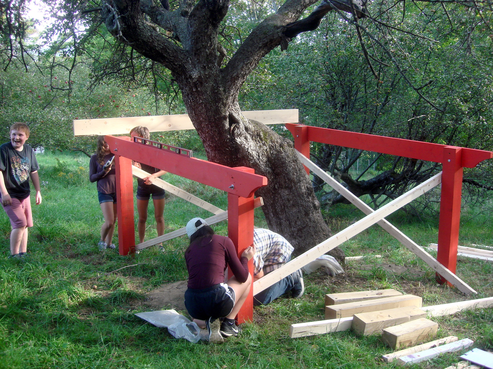 The group attaches 2x4's to stabilize the posts to each other and to prevent them from shifting during construction.