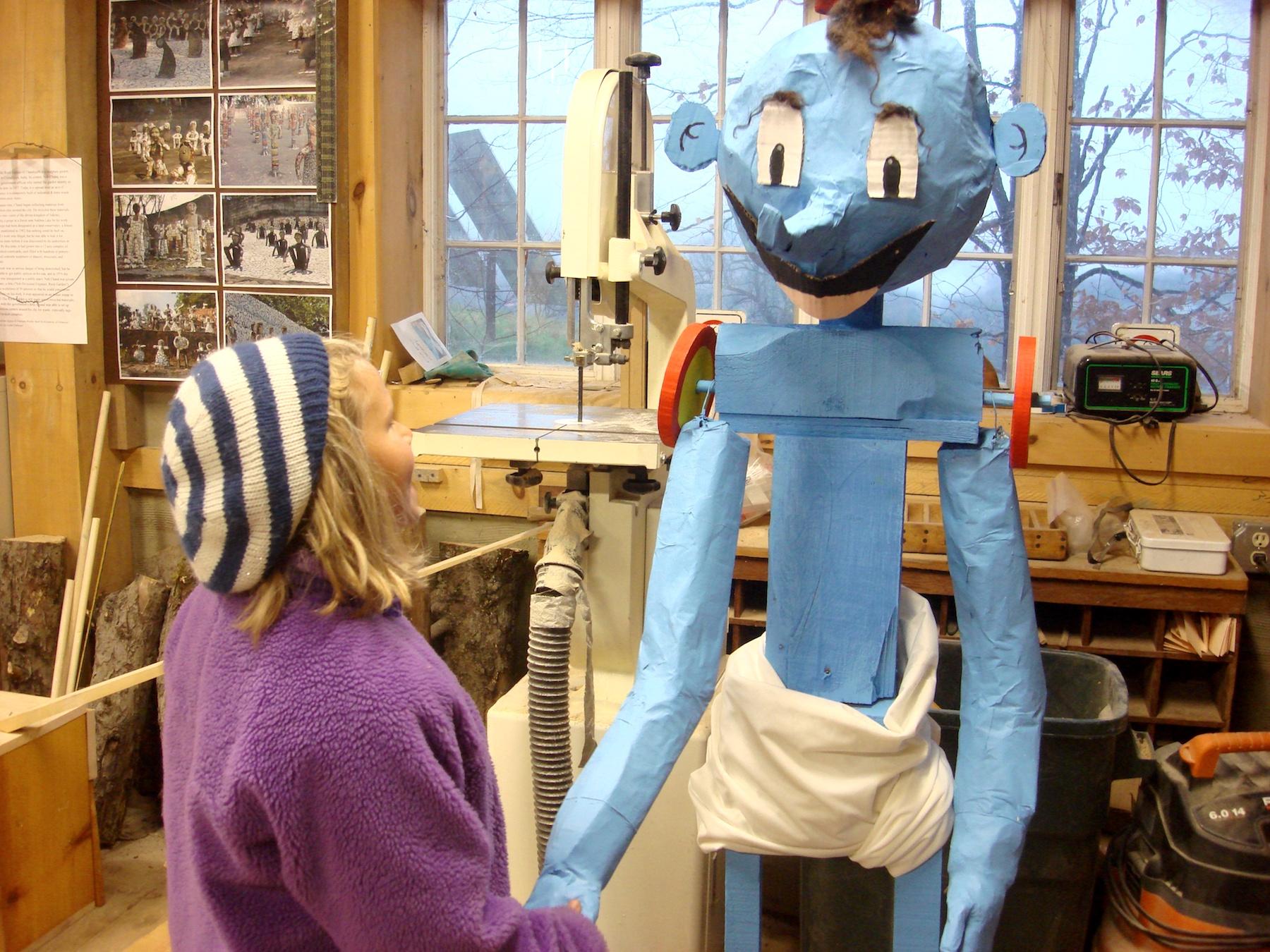 Annie shakes hands with Eddie's genie sculpture.