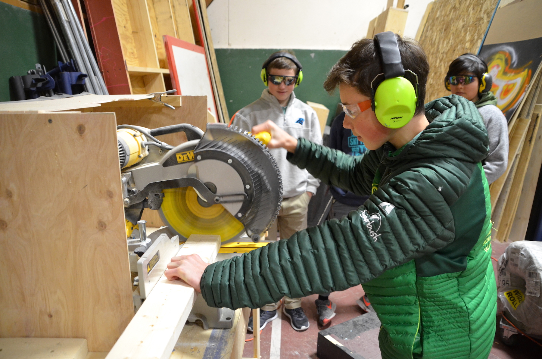 Tabor demonstrating how to make a cut with the miter saw.