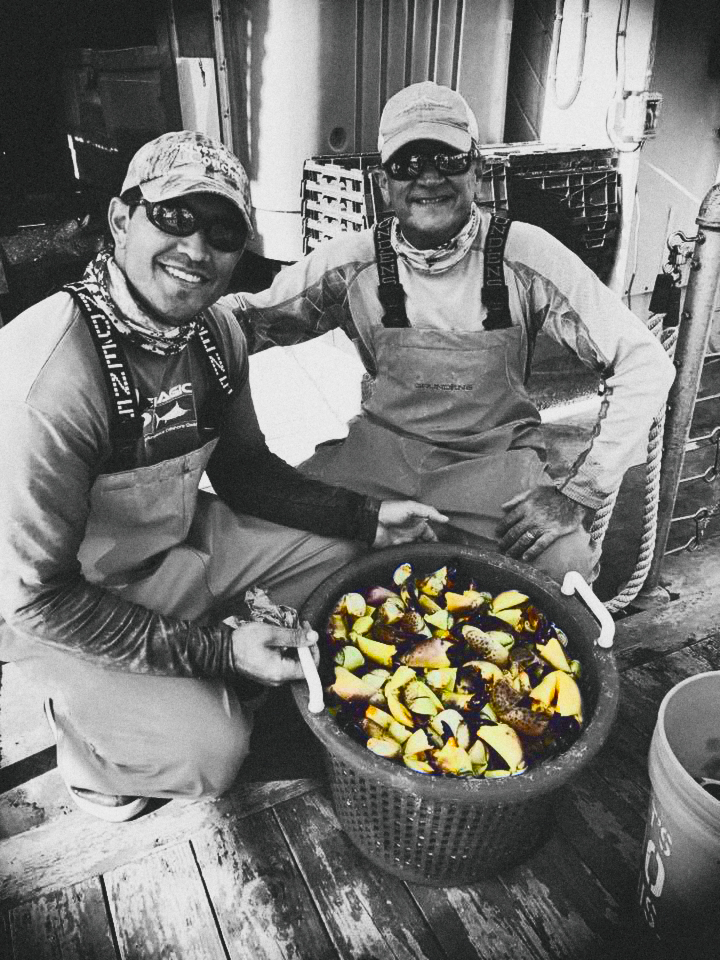 Capt Greg Orophza with mate and stone crab.jpg