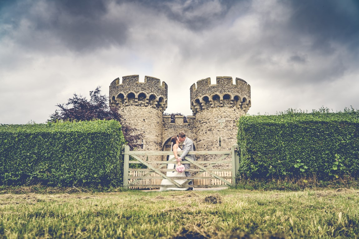 Bride and Groom by fence and castle turrets