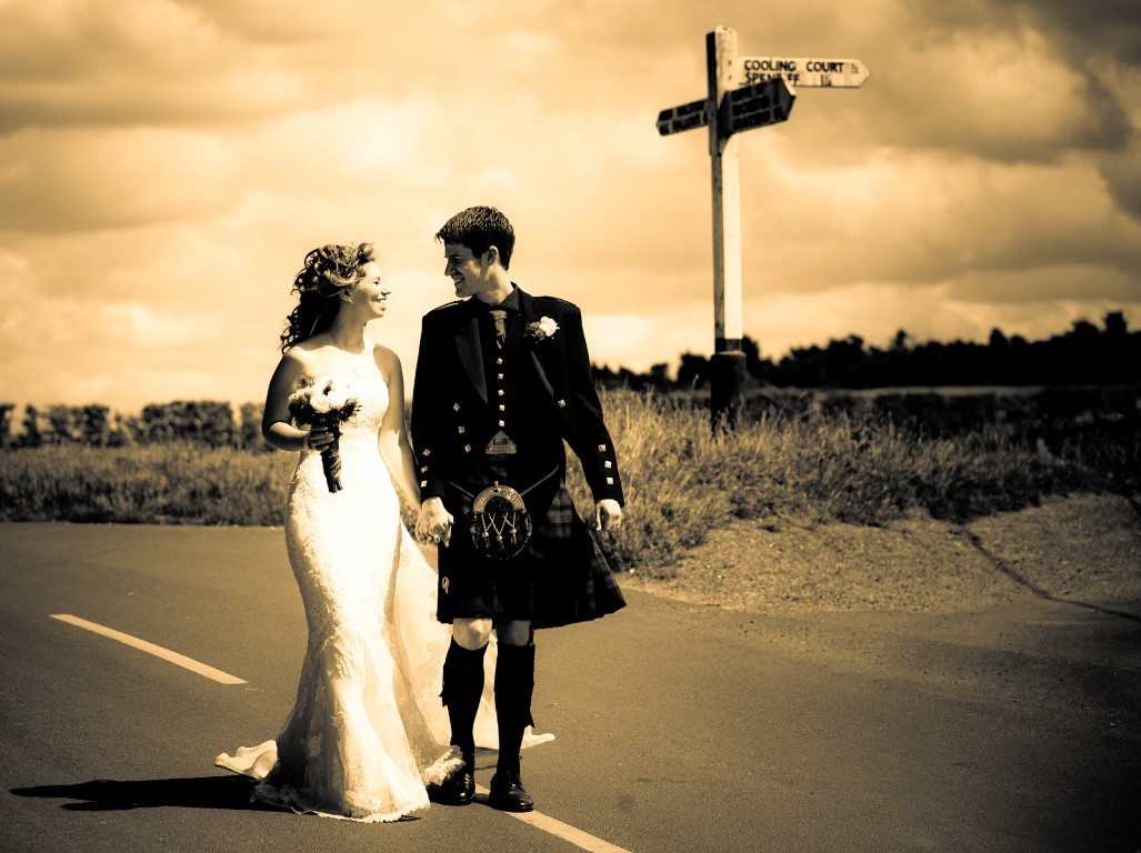 couple walking with vintage signpost in the background