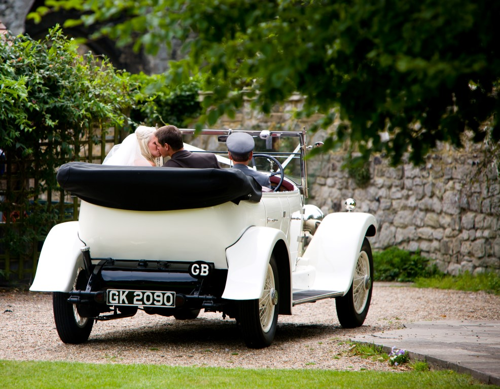 bride and groom in a car on the lawn