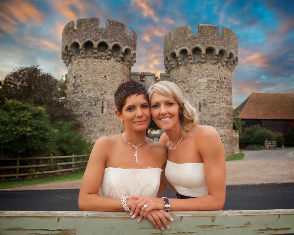 two brides leaning on the gate by the turrets