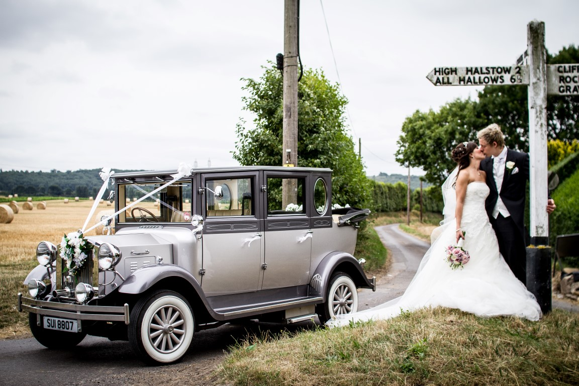 Bride and groom kissing with a car in the background