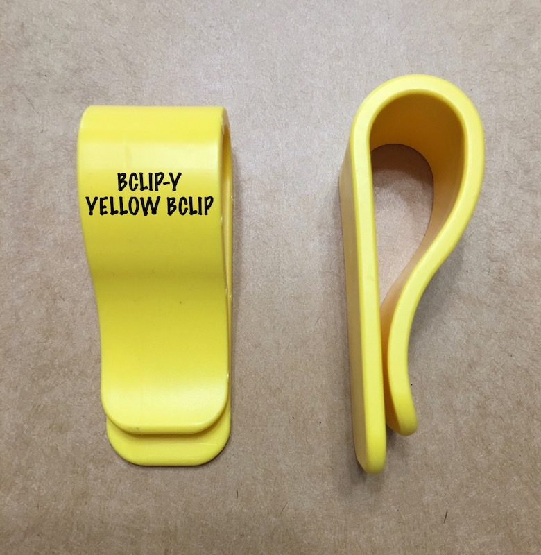 Red, yellow, and black plastic clips called BCLIPS box flap clips to hold box carton flaps open
