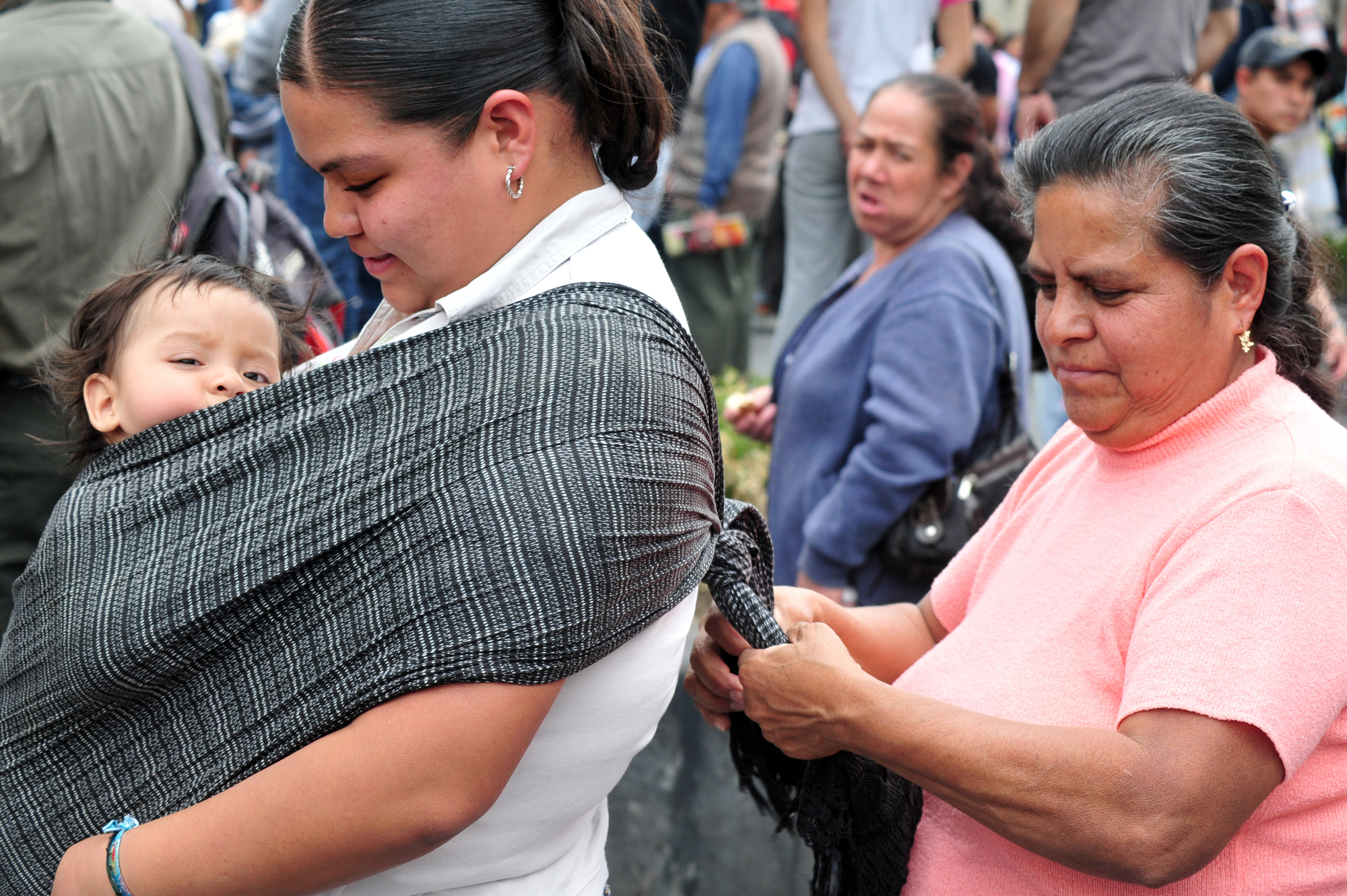 Woman ties mexican rebozo on mother to babywear