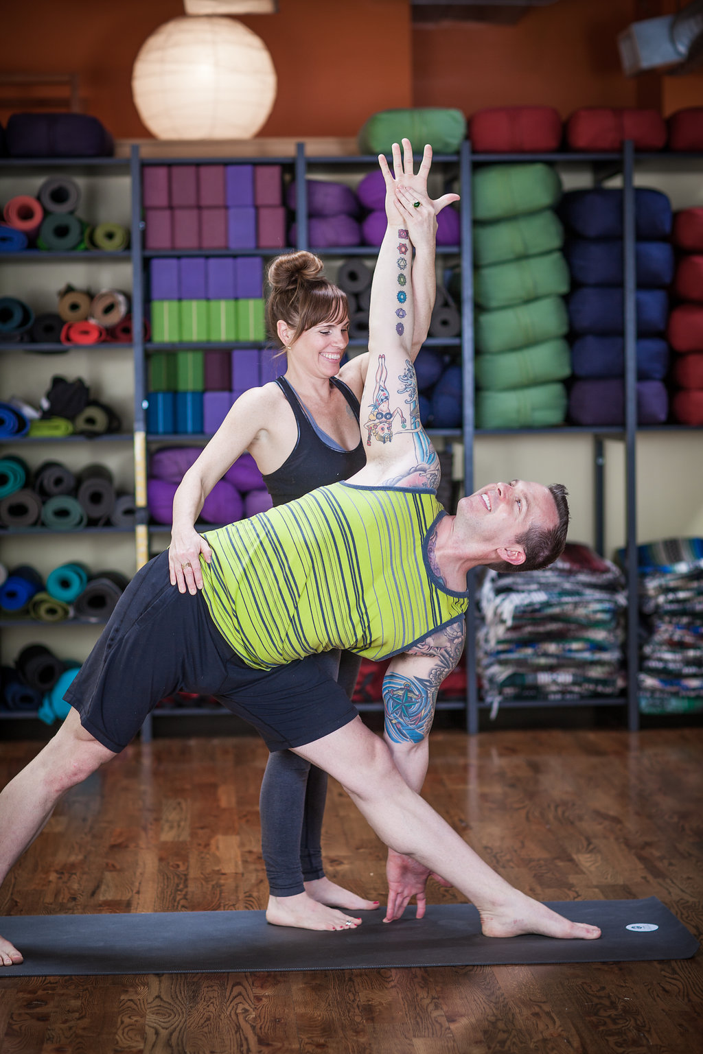 Yoga Teacher Assisting Student in Adho Mukkha Vrksasana (Hand STand) Pose