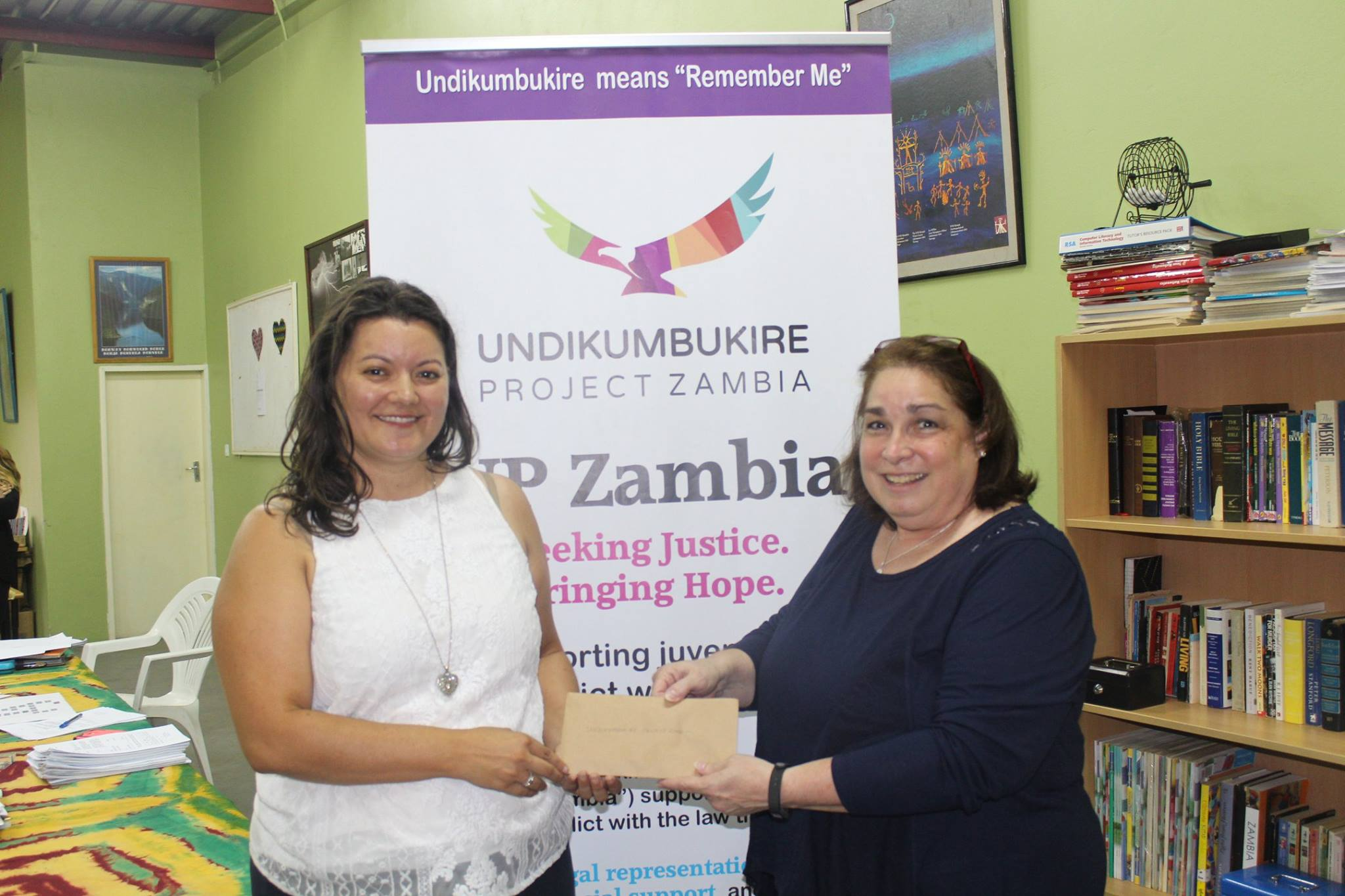 Nancy's mother, Cindy Czaicki, presents UP Zambia's founder Sara Larios with a donation from CIDRZ.