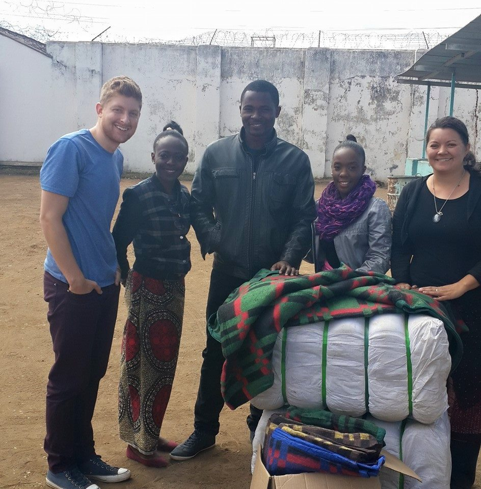 Adam with UP Zambia staff and volunteers outside Kamwala Remand Prison. That day, UP provided its regular educational/social/legal programs in addition to distributing 90 blankets to the juveniles housed there.